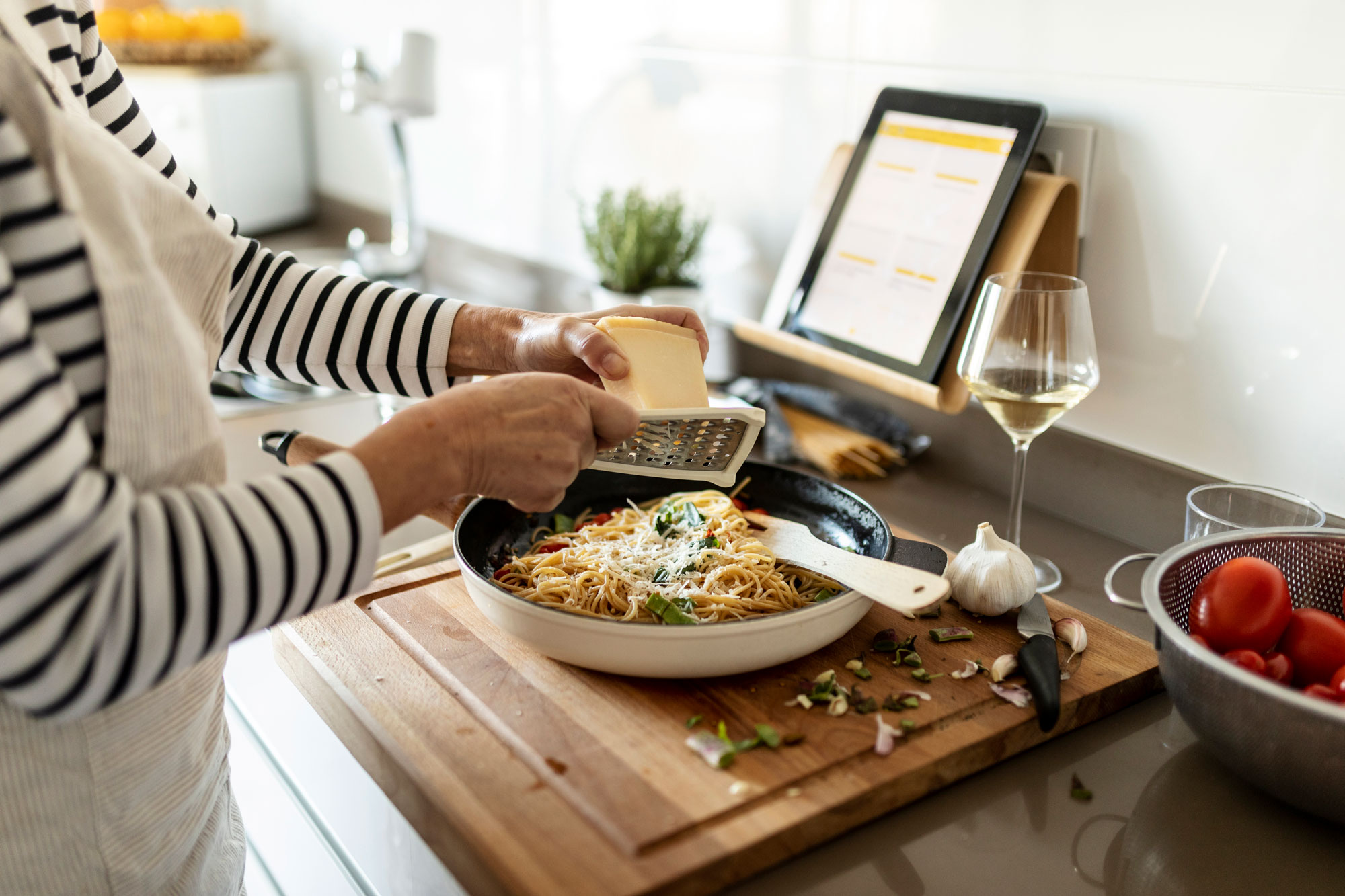 A person grating parmesan cheese into a skillet filled with spaghetti.