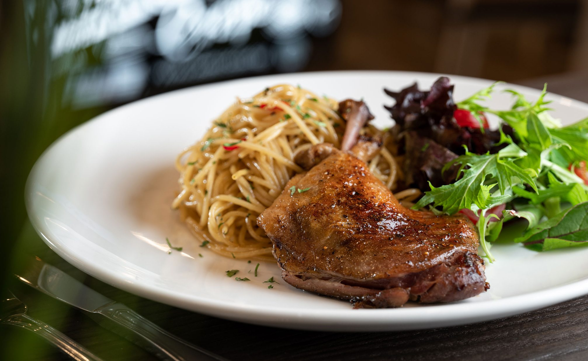 A white dinner plate filled with duck, spaghetti and salad.