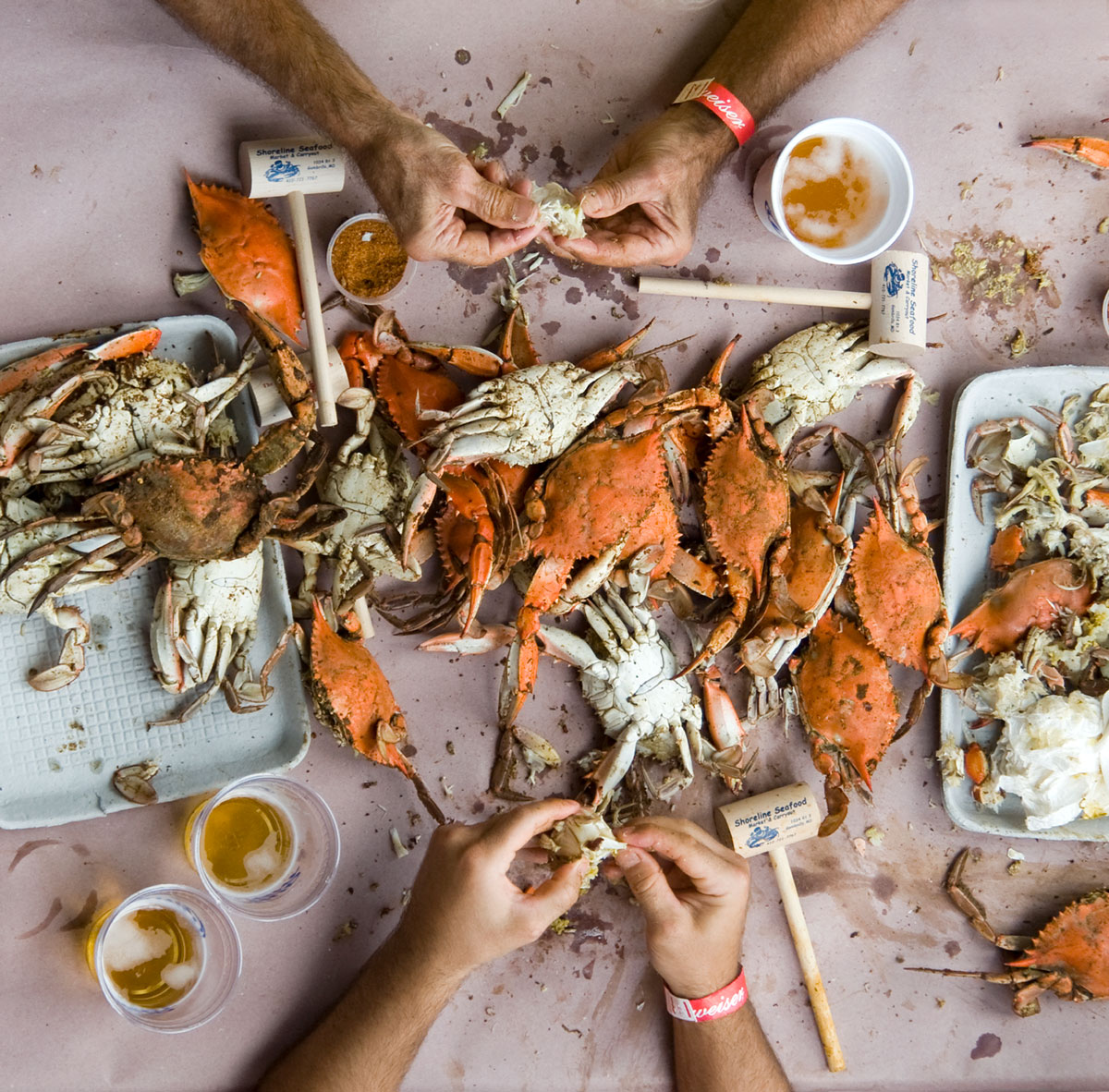 A crab boil feast strewn about a table as a person enjoys.