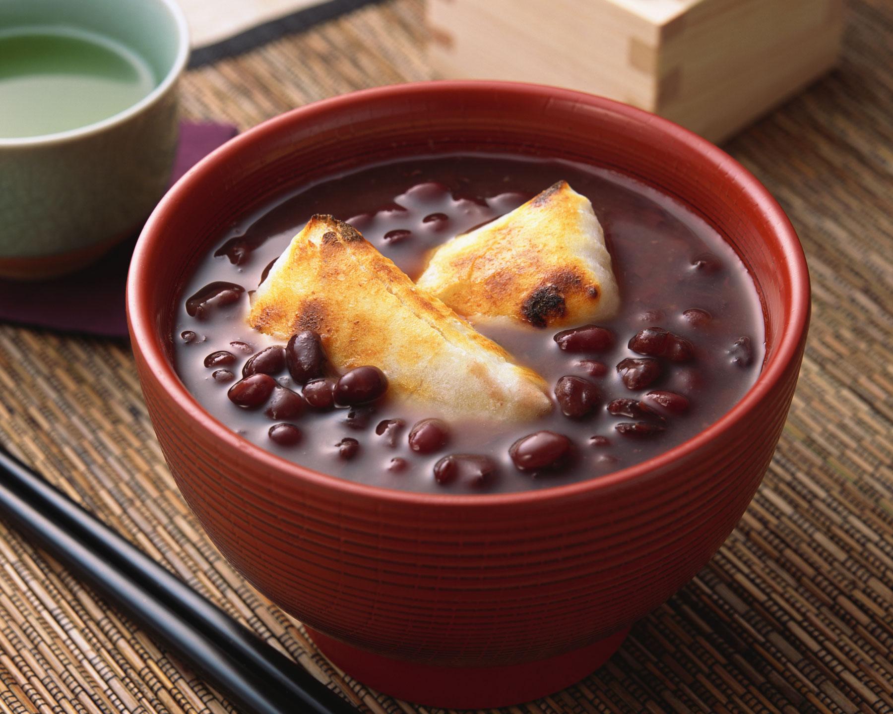 A sweet red bean soup in a dark orange bowl.
