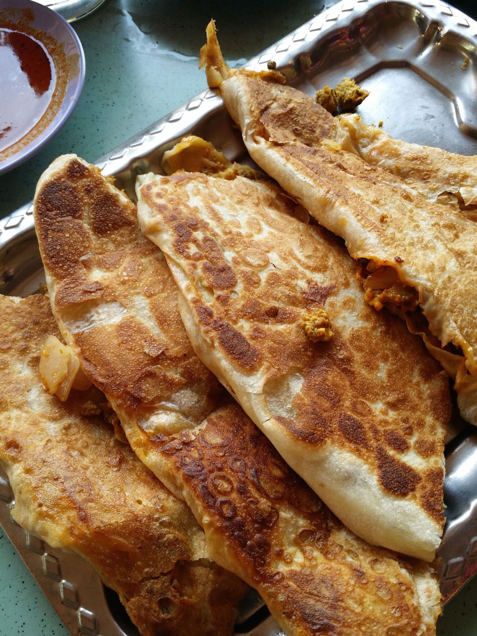A silver plate filled with Roti Prata.