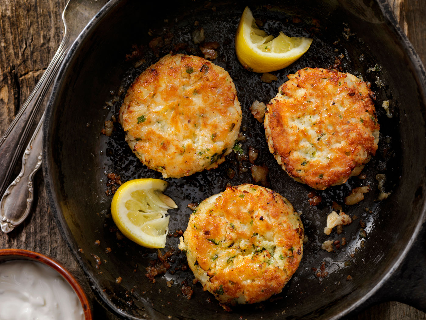 Three crab cakes frying in a skillet with sliced lemon.