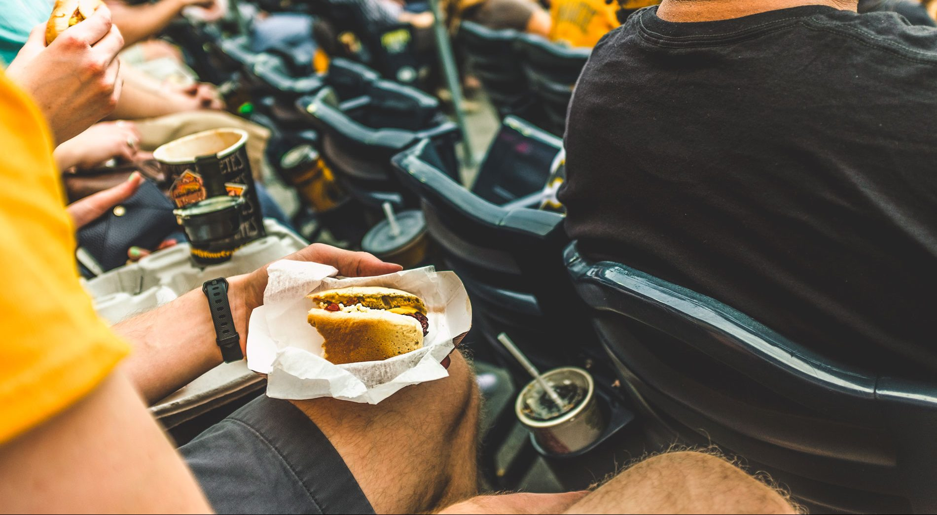 A person eating oversized hot dog in a baseball stadium.