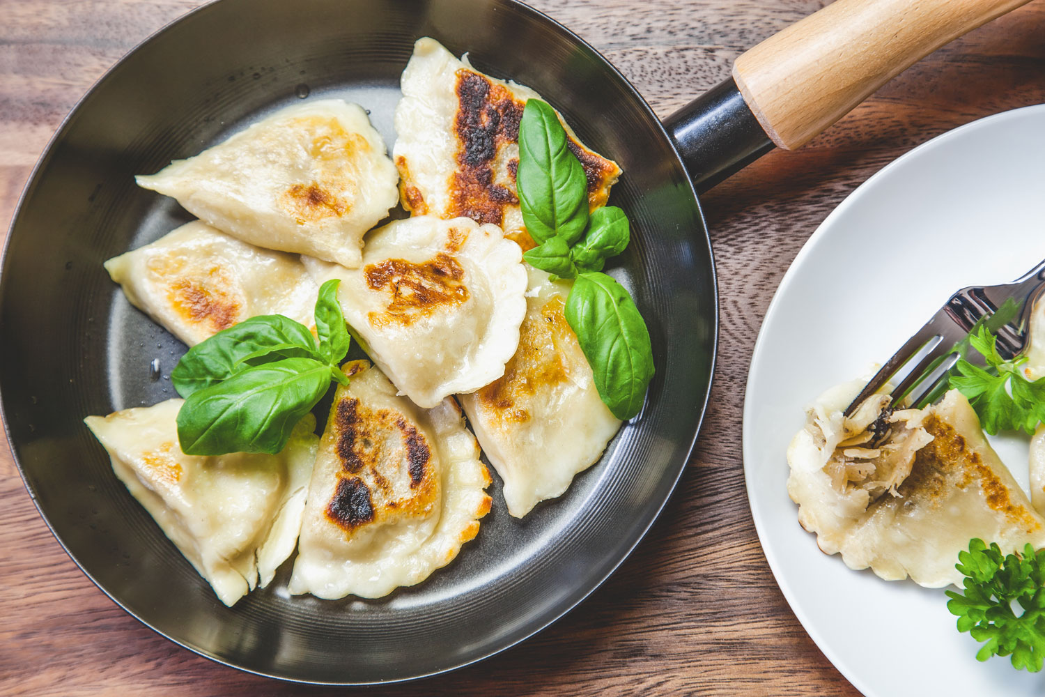 A pan filled with fried pierogies garnished with basil.