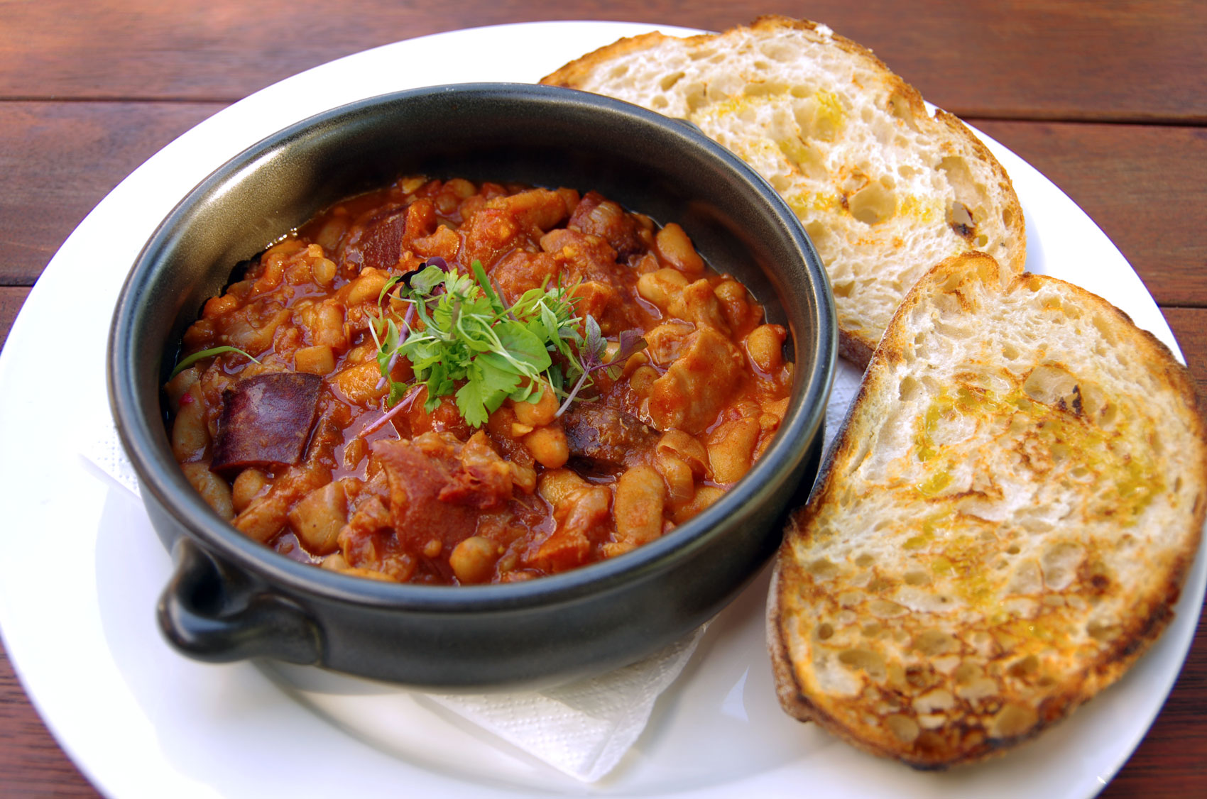 A black bowl filled with spicy New Orleans red beans and rice with a side of toasted bread.