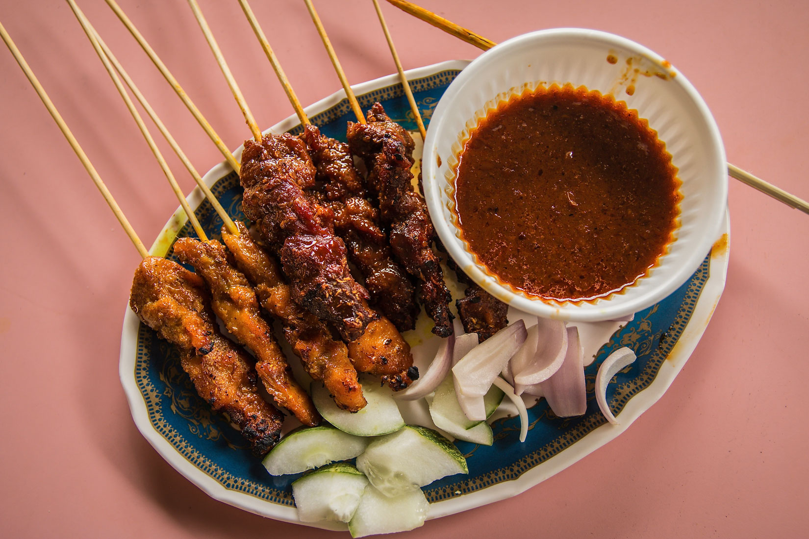 An ornate dish filled with Singaporean satay and a dish of peanut sauce.