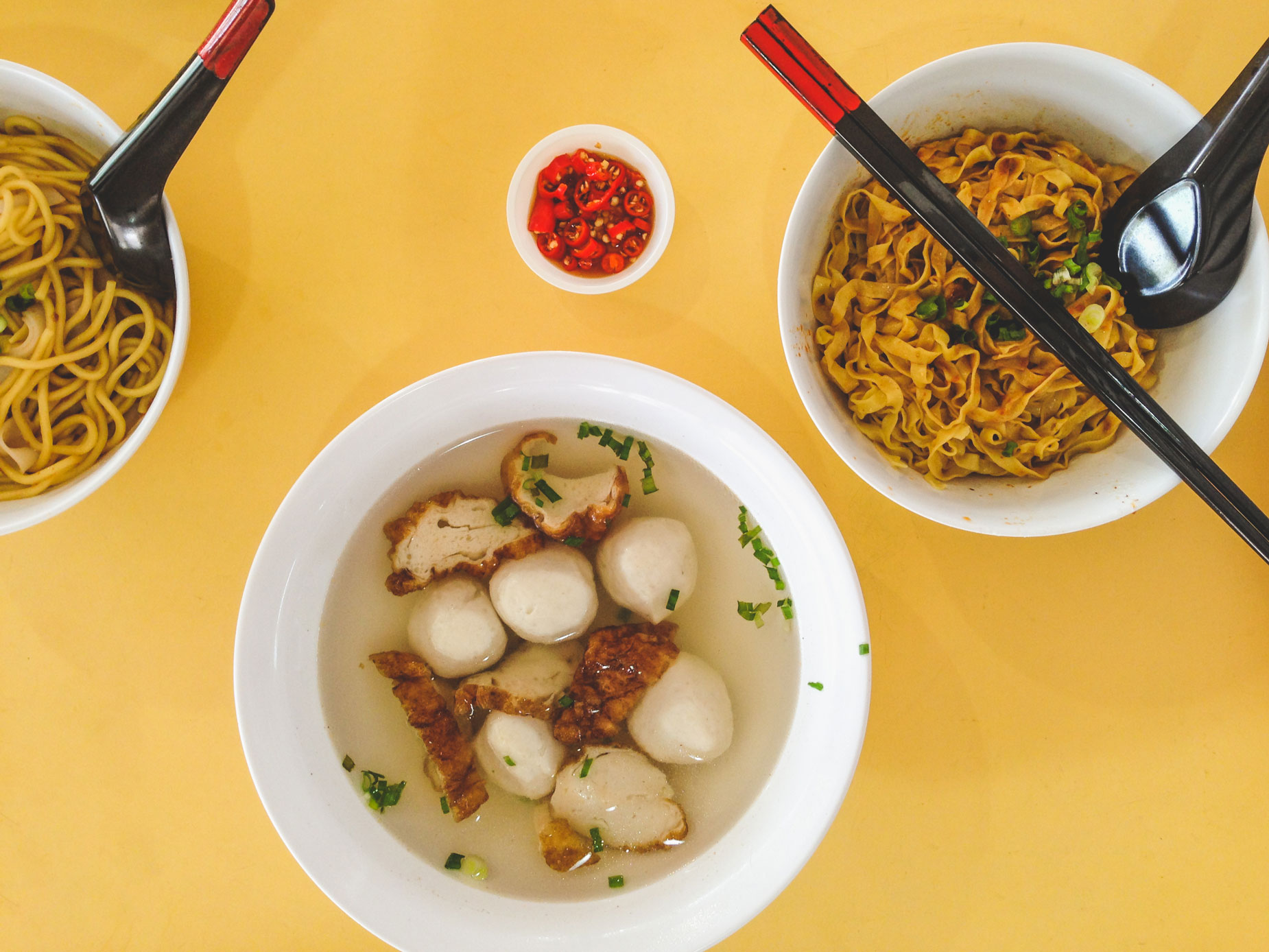 Bowls of Singaporean noodles and soup on a bright yellow table.