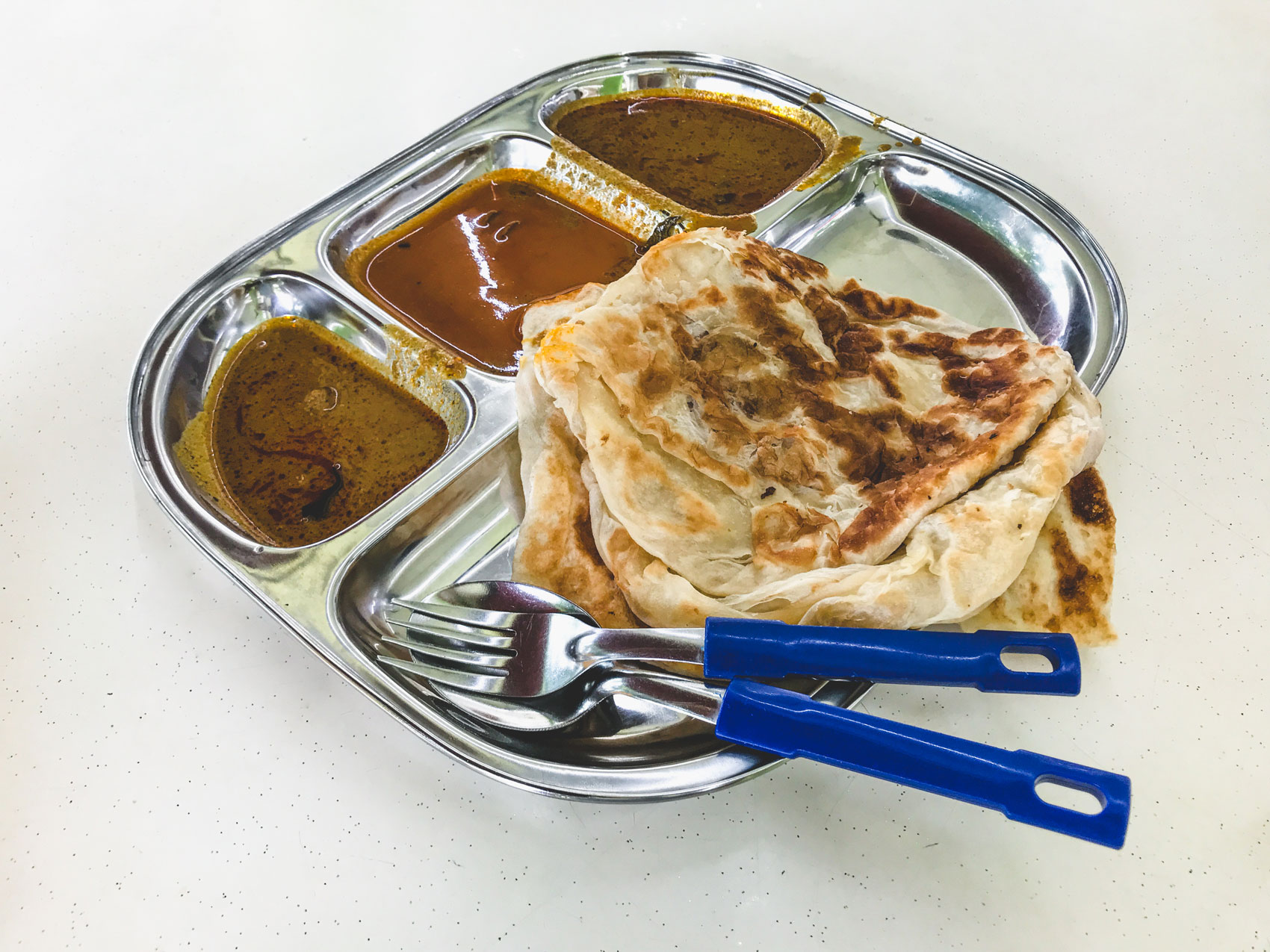 A silver tray filled with Roti John and a variety of sauces.