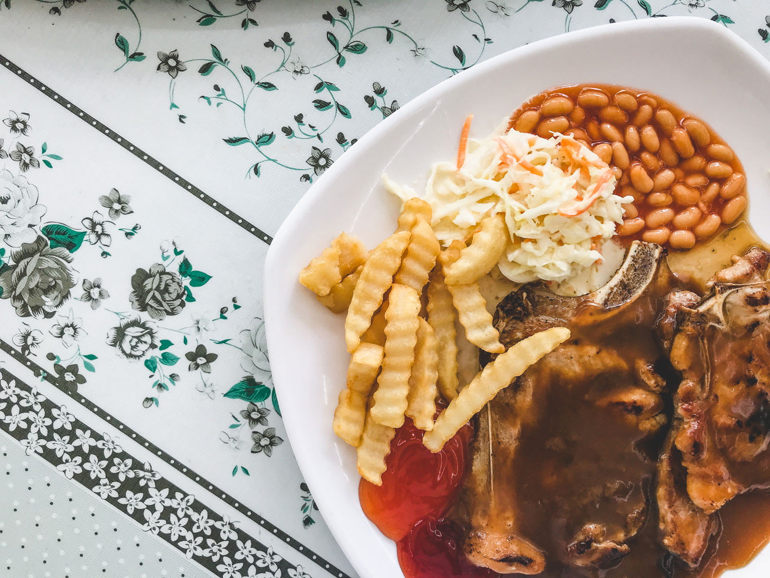 A plated porkchop in brown sauce served with crinkle-cut fries, baked beans and coleslaw.