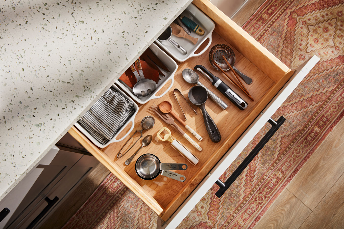 An open kitchen drawer filled with utensils neatly organized.