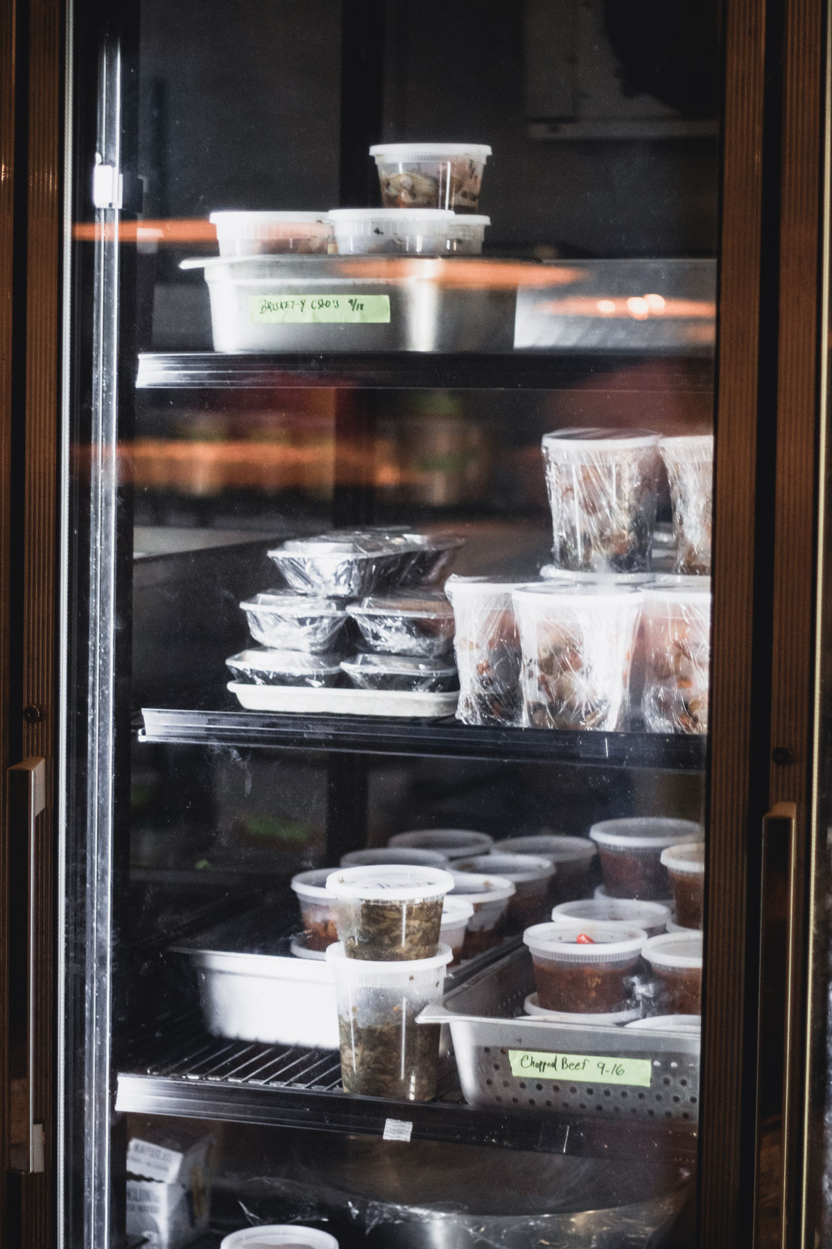 A refrigerator filled with containers of assorted meats, briskets and other eats.