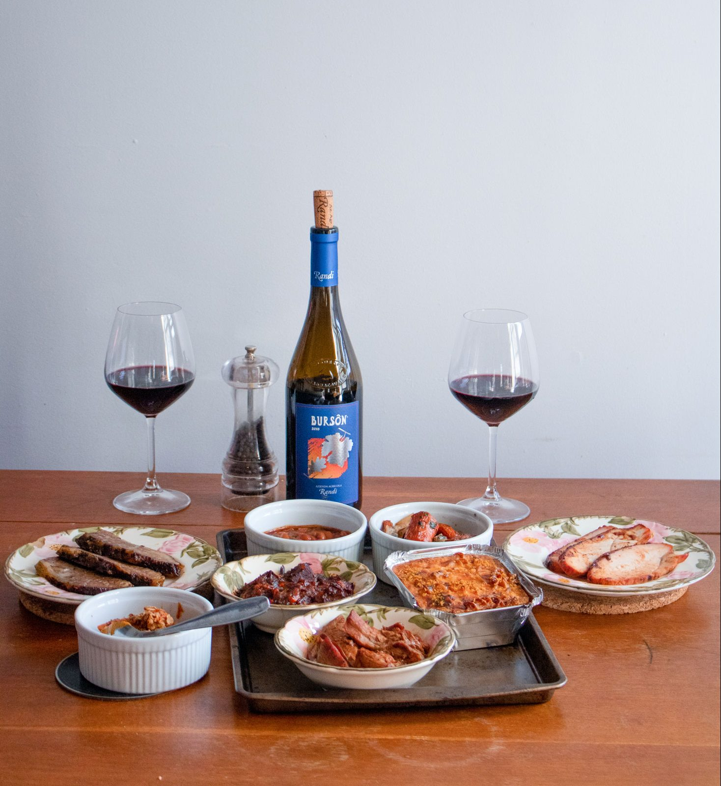 A table with an open bottle, two filled wine glasses and other dishes.