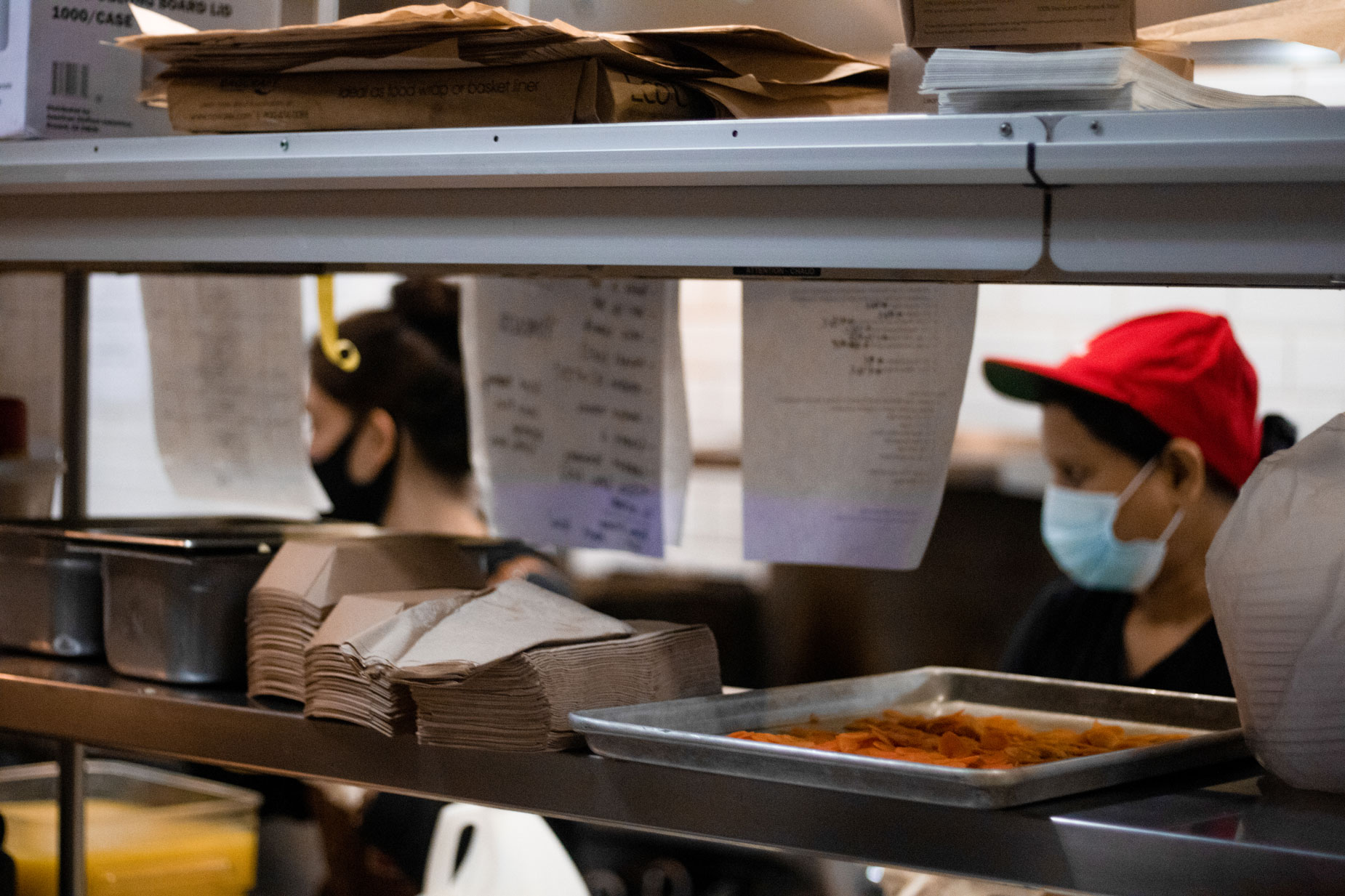 Kitchen order tickets strewn about for workers to fulfill.