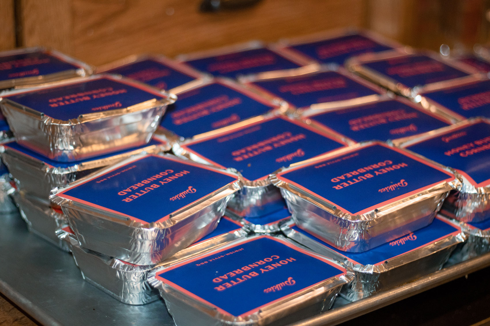 A series of sealed foil containers filled with honey butter cornbread.