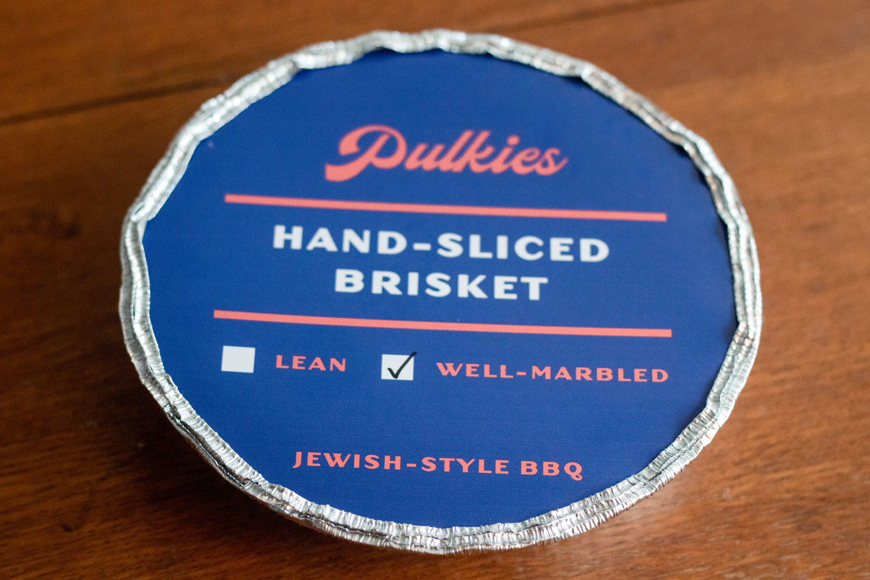 A sealed circular foil container filled with hand-sliced brisket.
