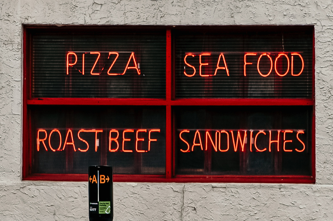 Four red neon signs displaying various types of food.