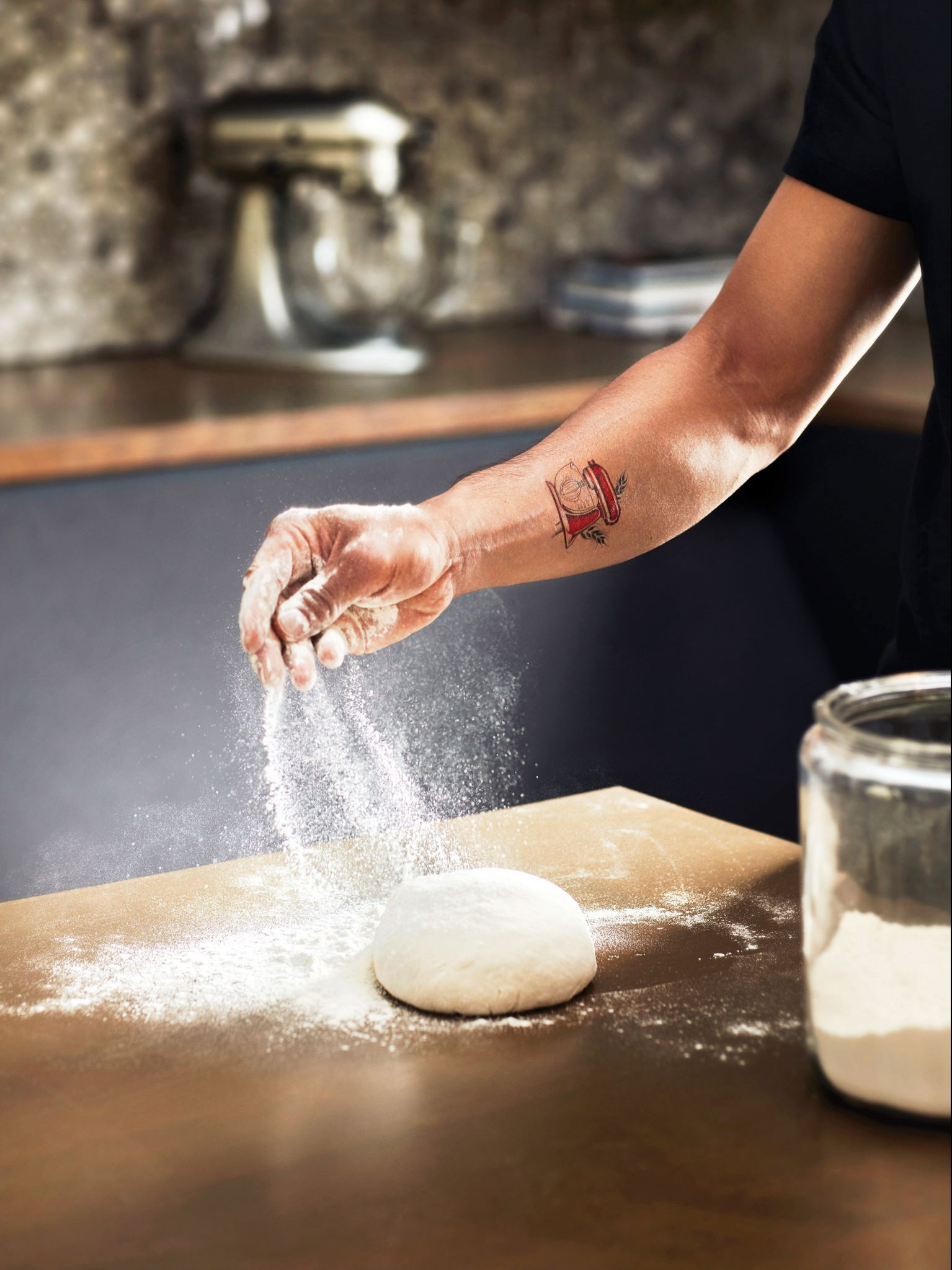 A person sprinkling flour on fresh dough.