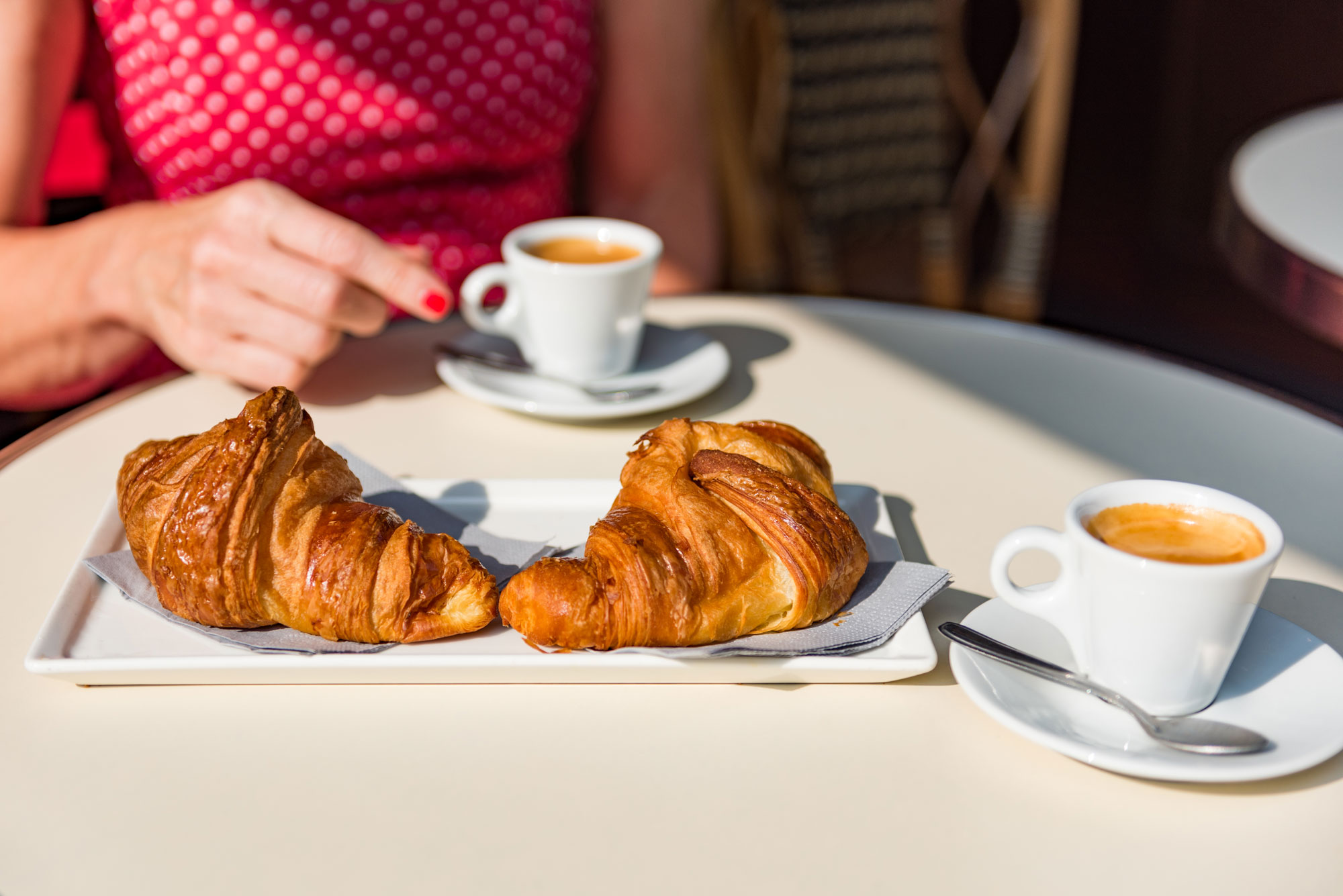 Two croissants on a delicate white dish.