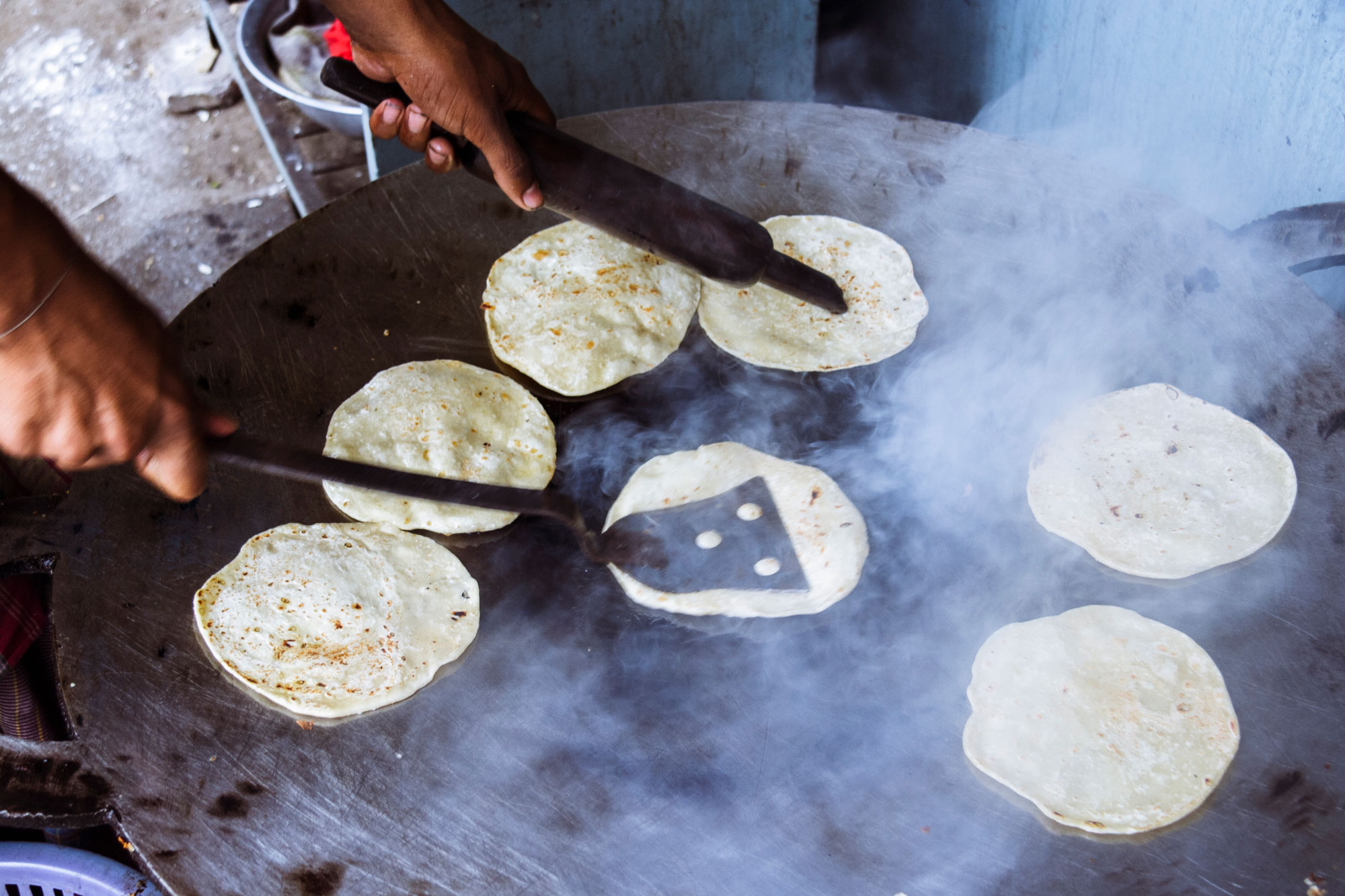 A person cooking small paratha flat bread.