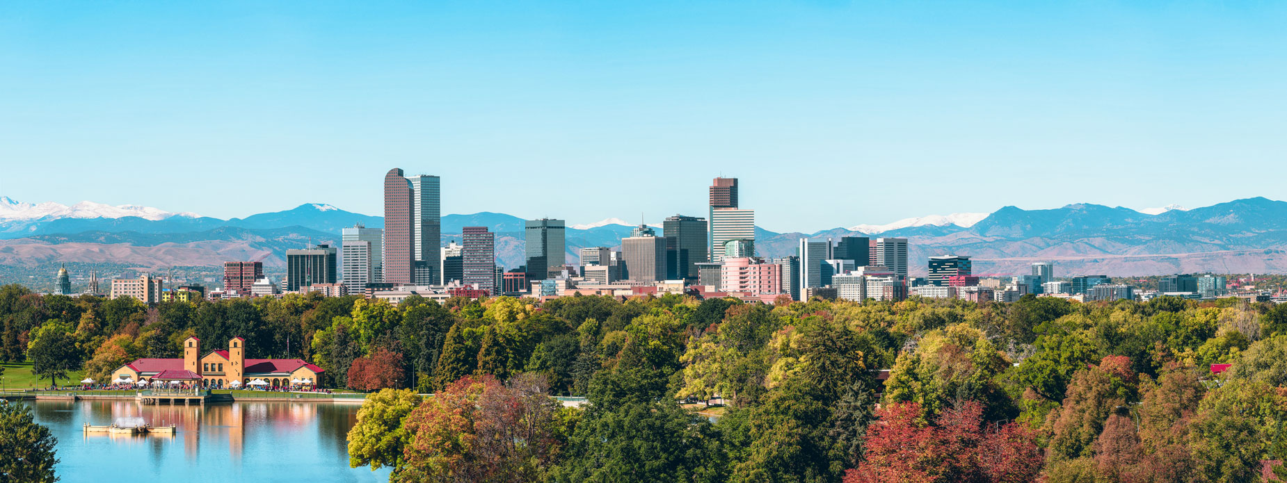 The city of Denver surrounded by picturesque mountains and colorful trees.