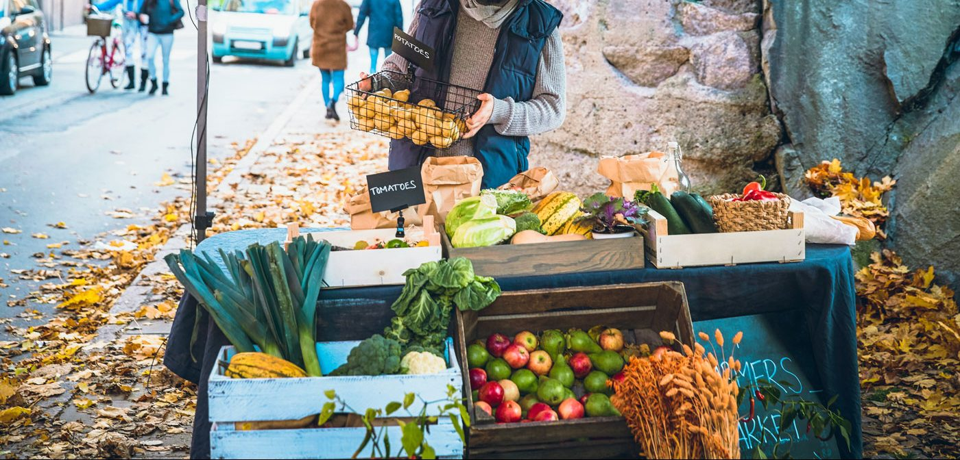A person arranging a vegetable stand filled with organic vegetables.