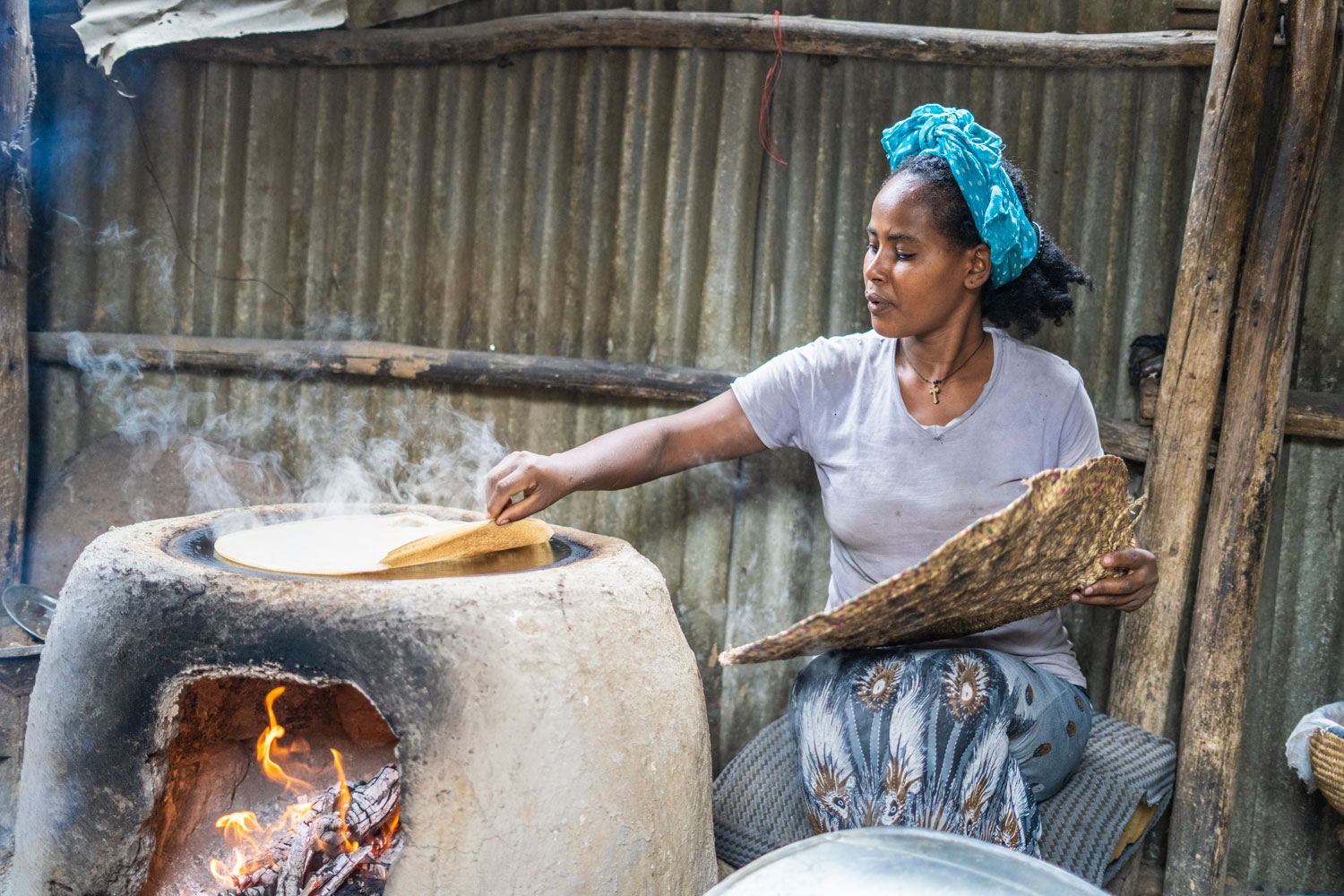A woman slowly lifting the edges of Ethiopian flatbread.