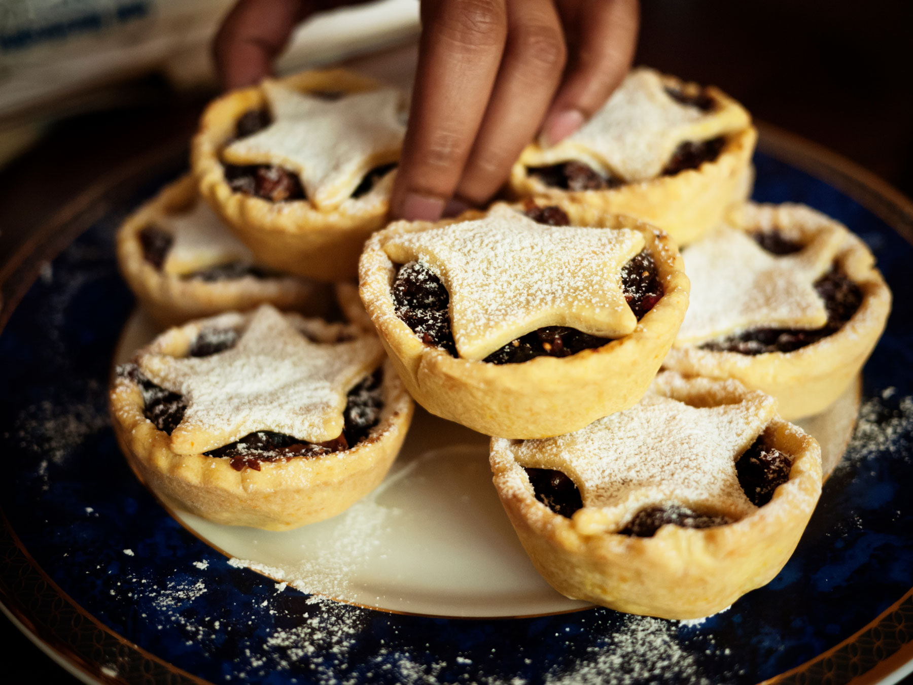 A dish filled with mini, starred mince pies.