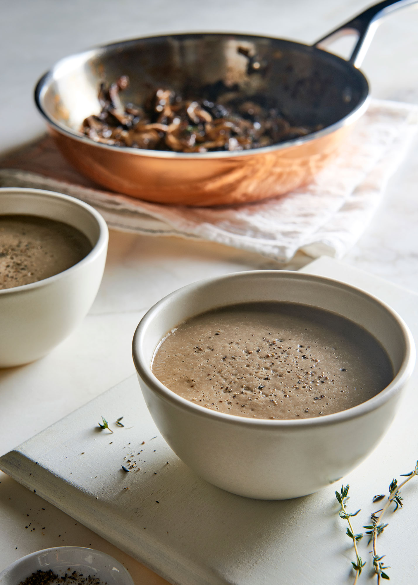 Two white bowls of creamy magic mushroom soup.