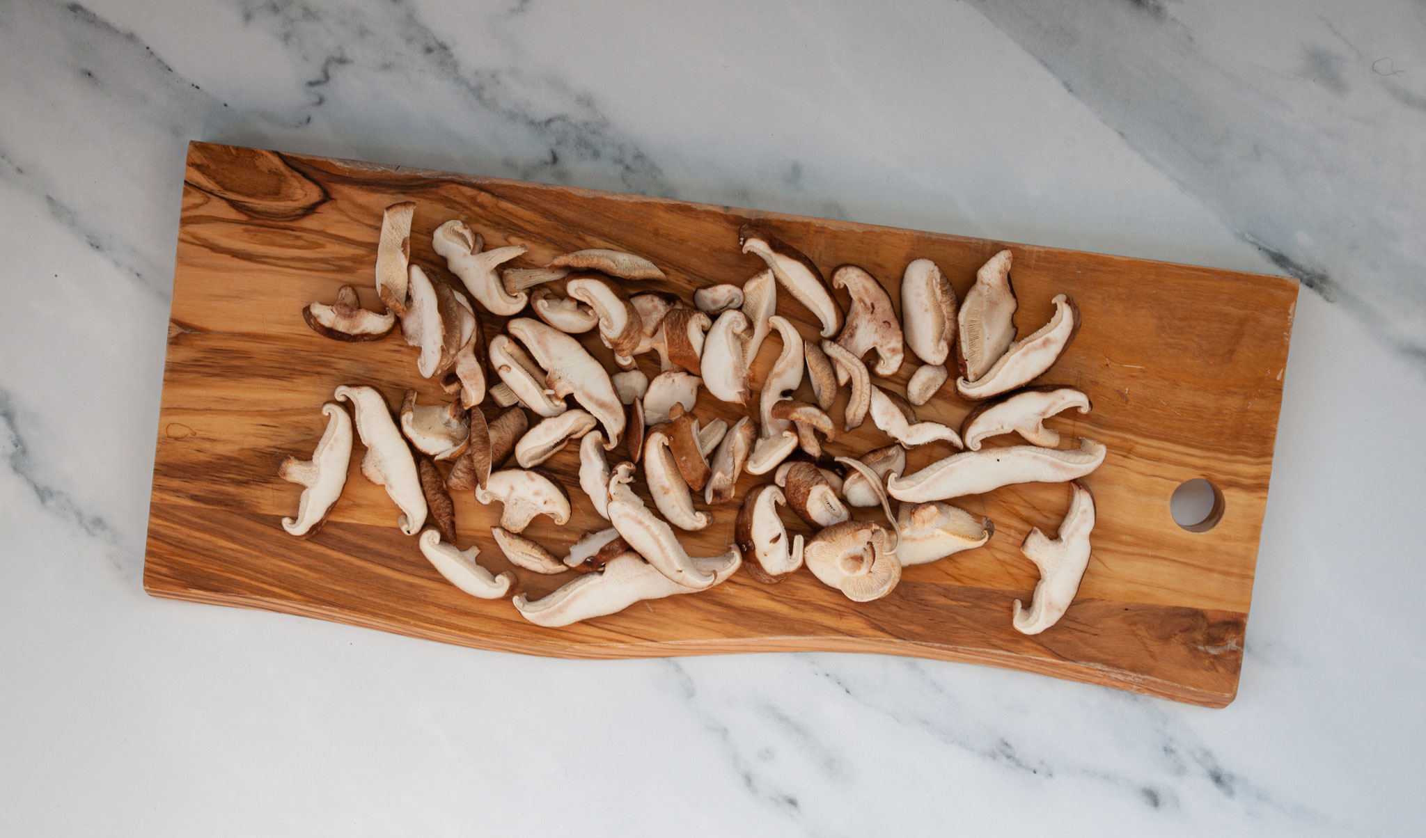 Sliced mushrooms resting on a wooden cutting board.