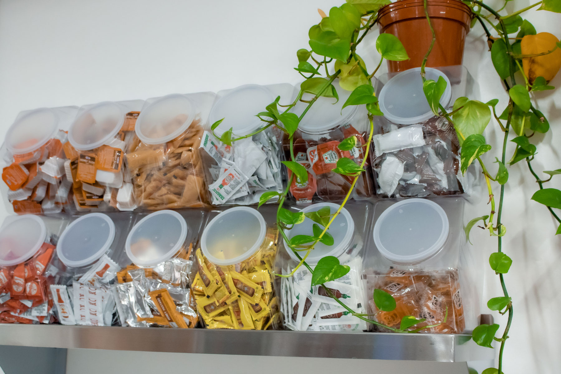 Individual storage containers filled with a variety of sauce packets and containers.