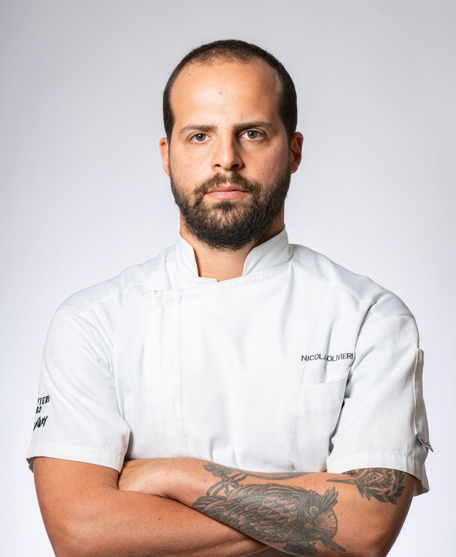 A professional portrait of Nicola Olivieri in his chef's uniform.