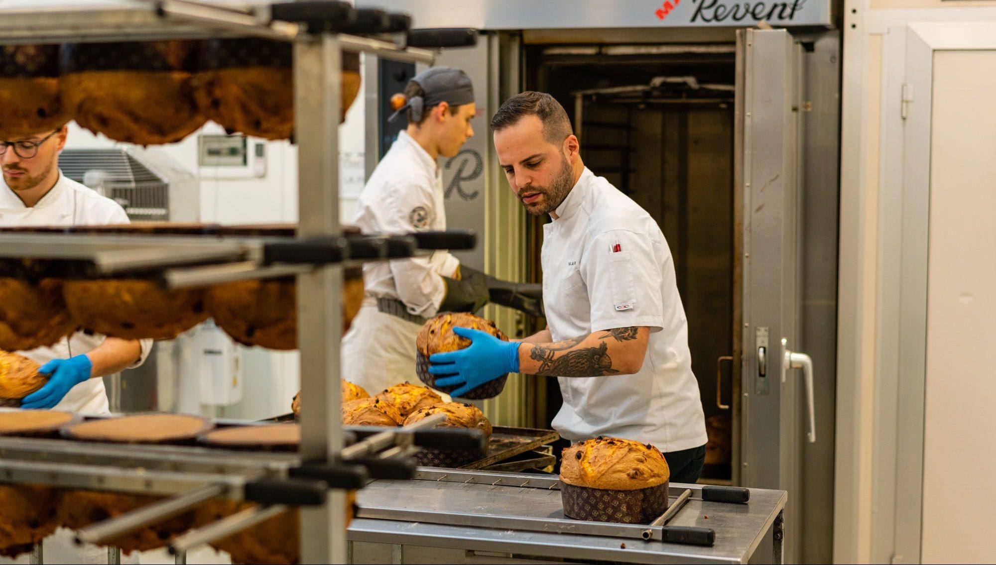 Olivieri handling freshly baked panettone loaves.