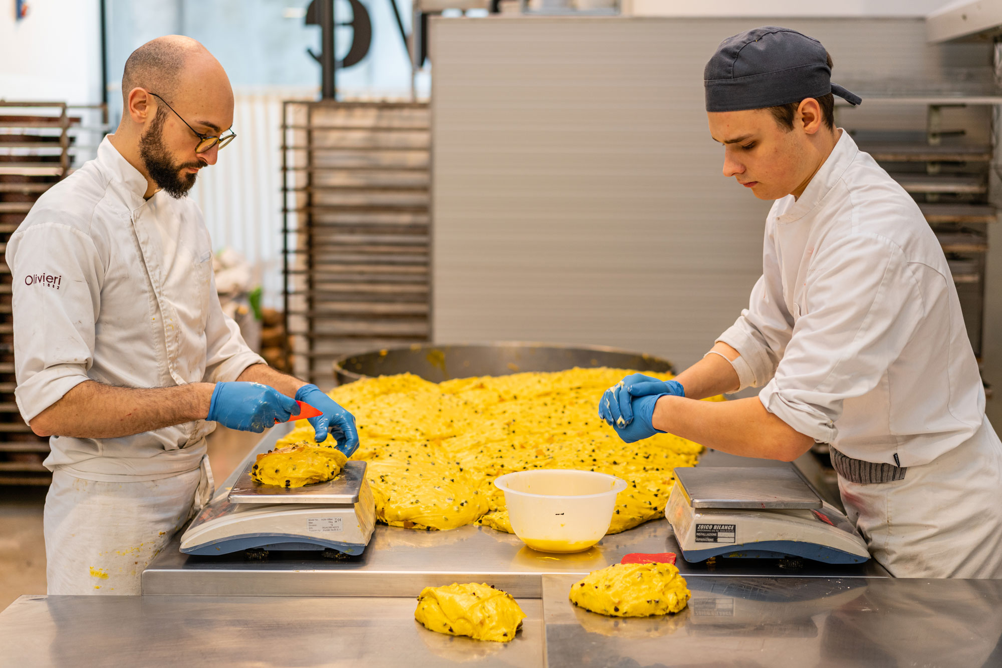 Bakers carefully portioning panettone dough.