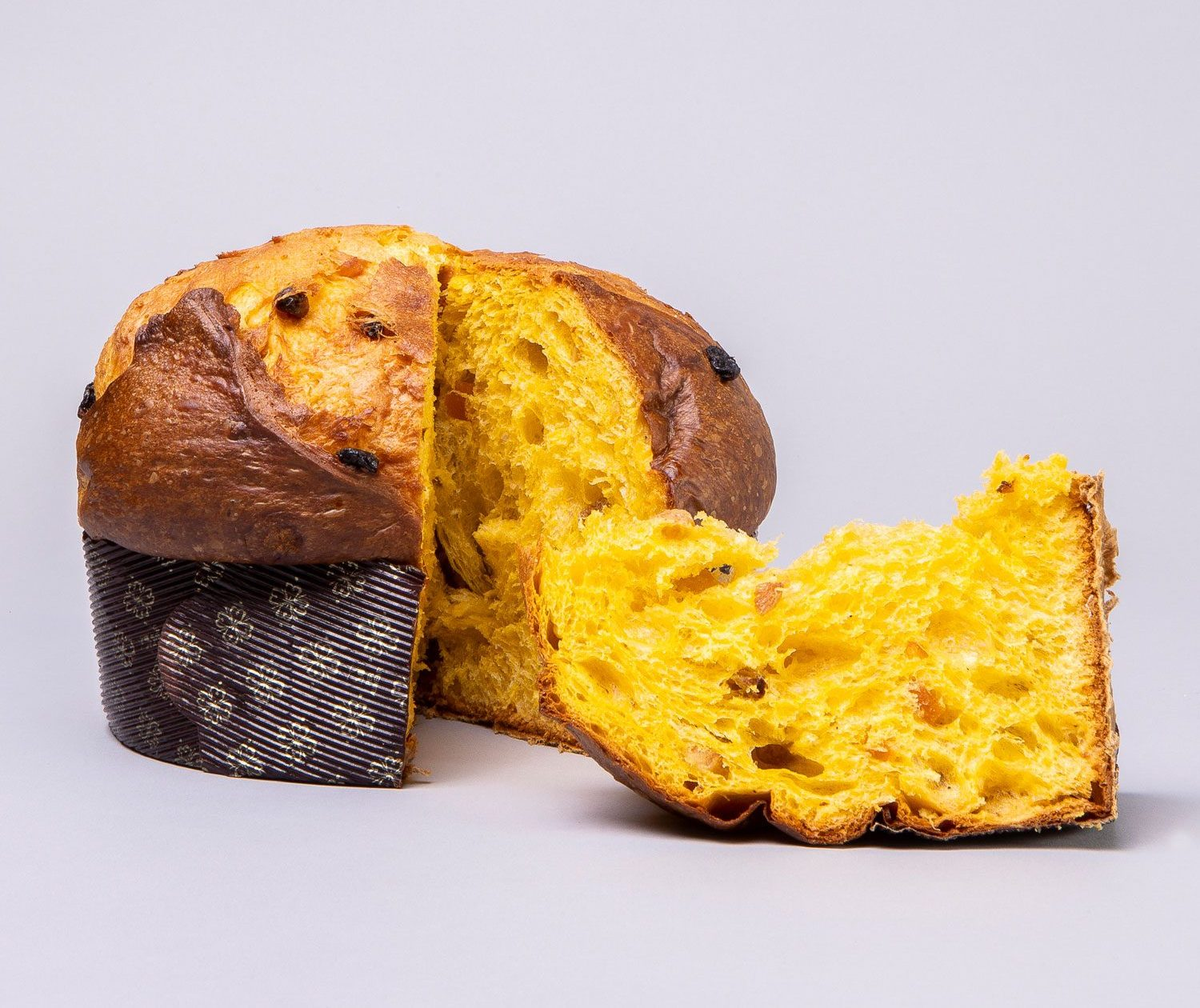 A loaf of panettone with a clean slice resting next to it.