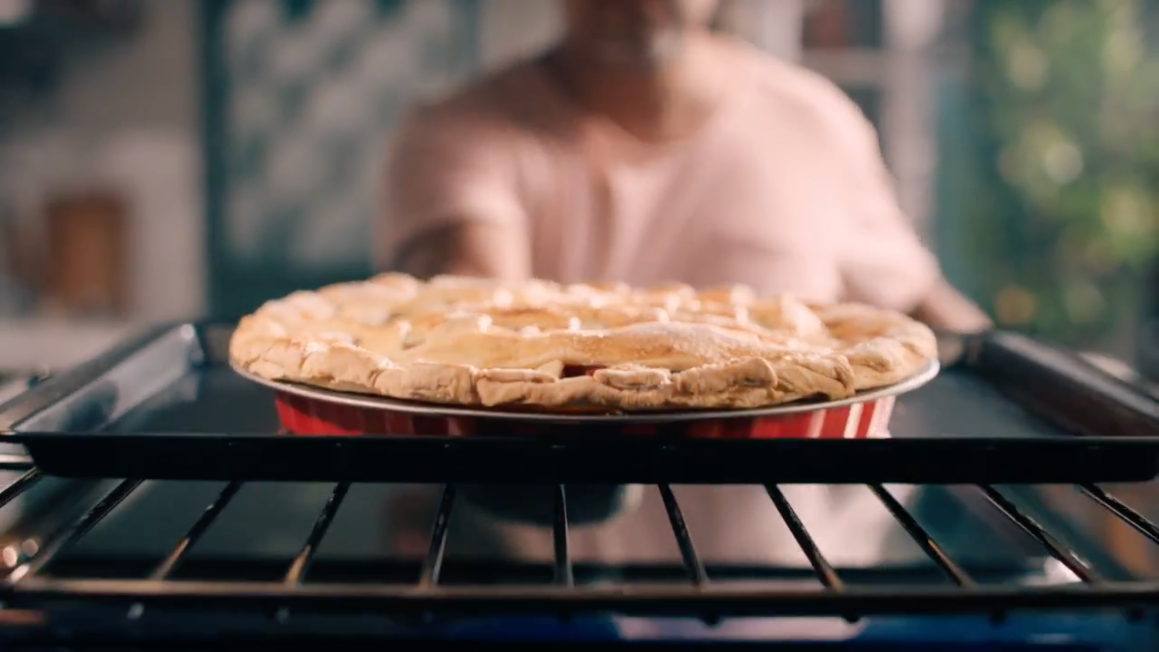 A person pulling out a pie from the oven.