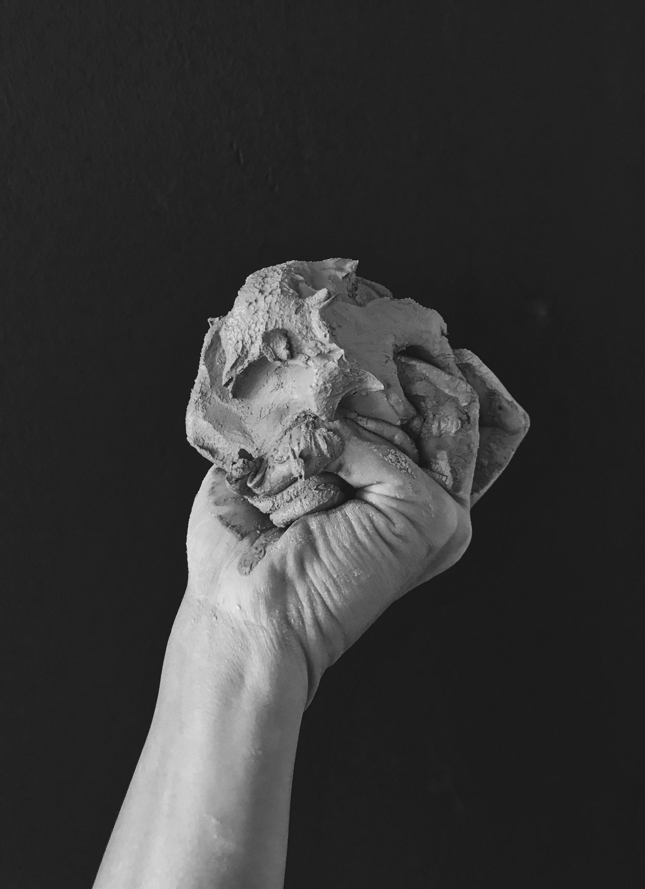 A hand holding a large wad of clay.