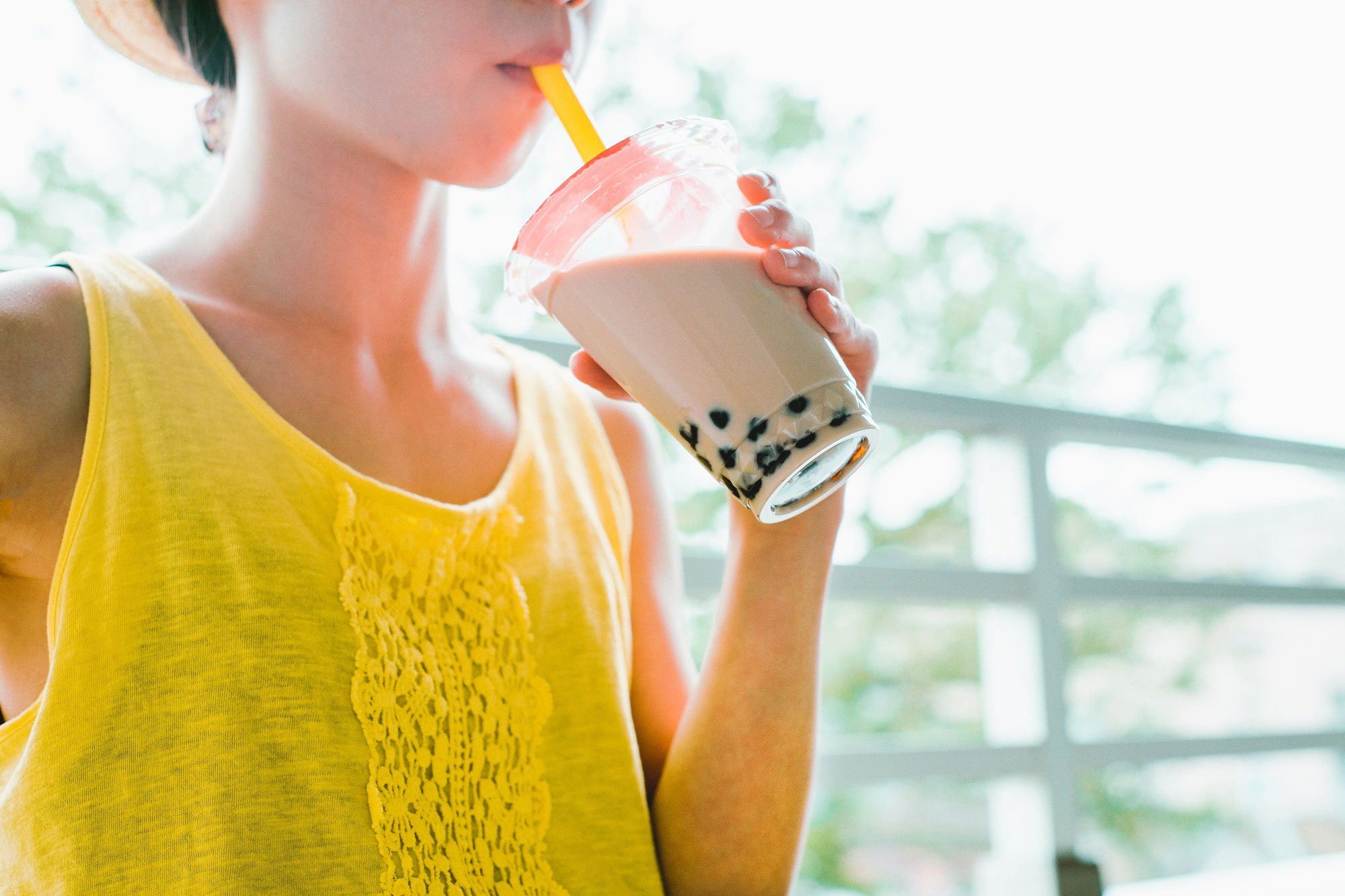 A person happily drinking boba tea.