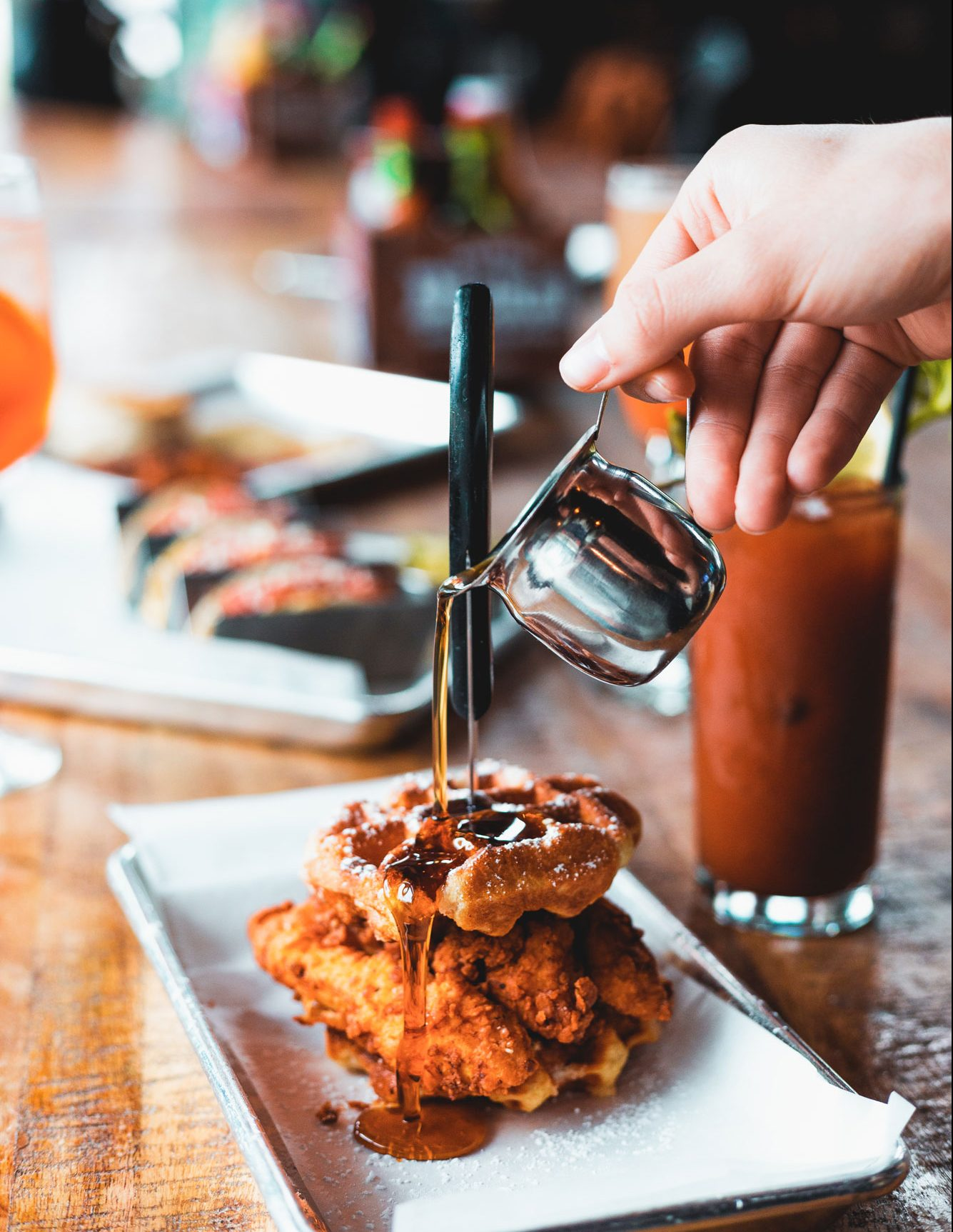 A person pouring syrup on a plate of chicken and waffles.