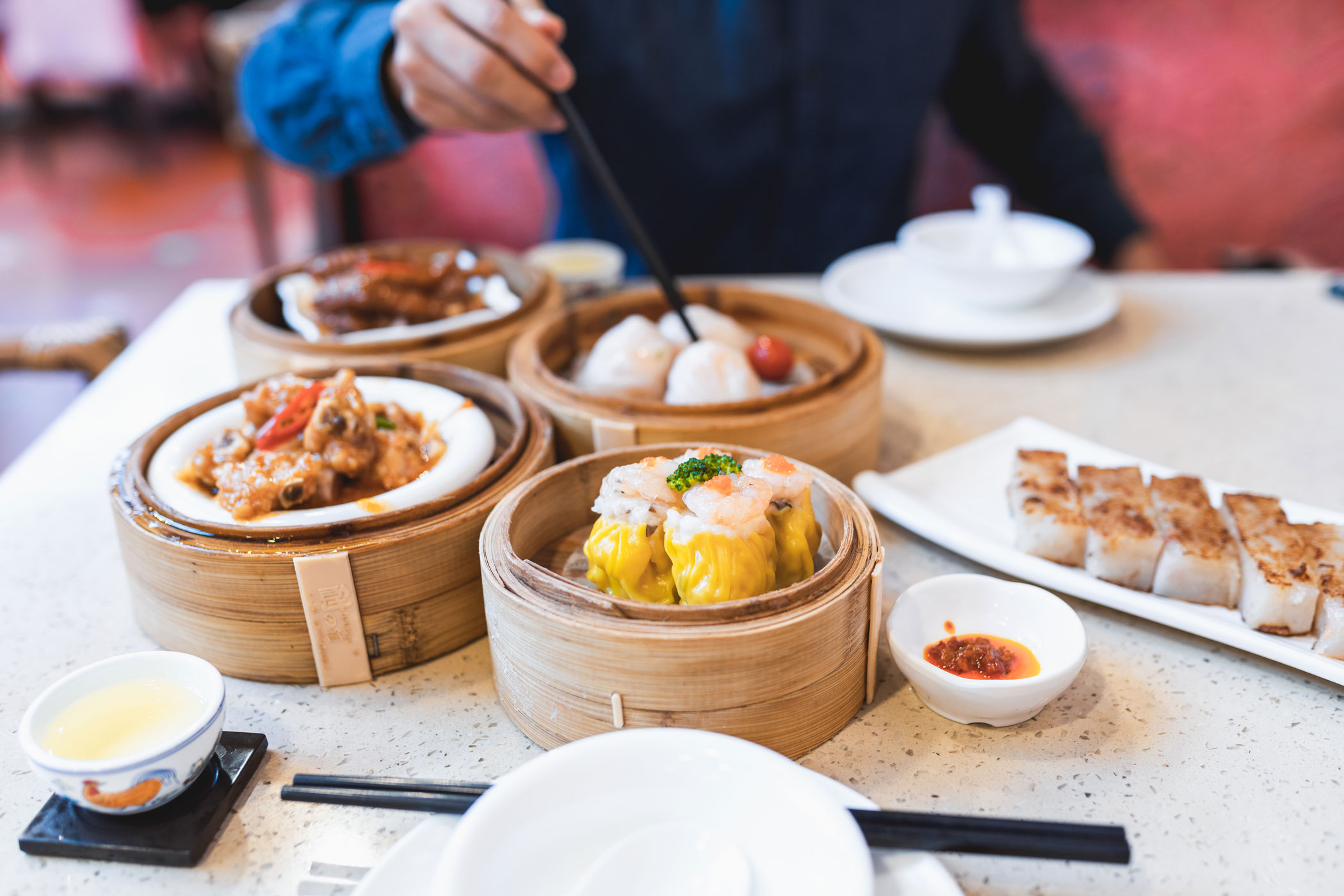 A person enjoying lavish dishes of dim sum with another person.