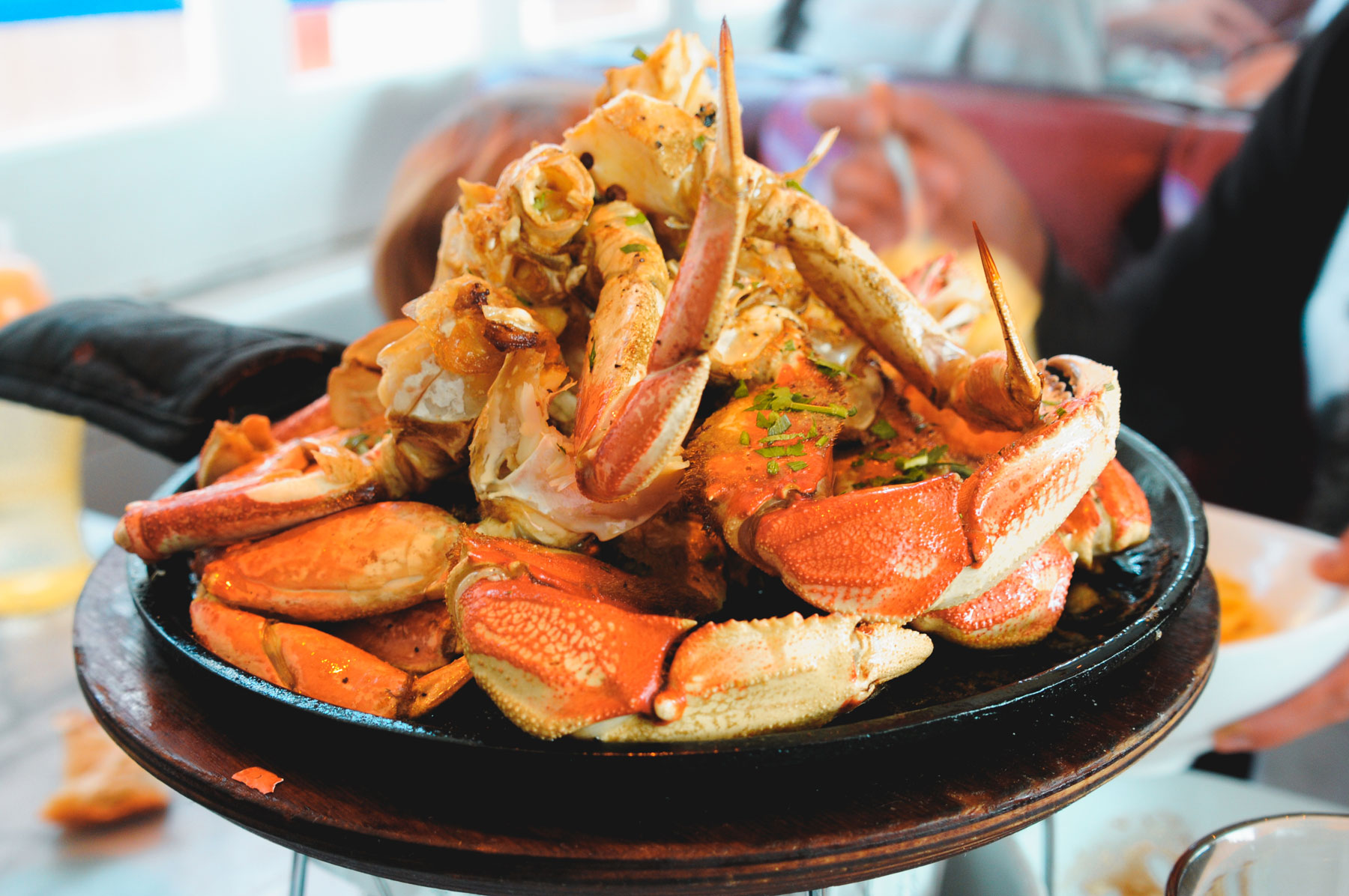 A cast iron skillet filled with steamed crab legs.