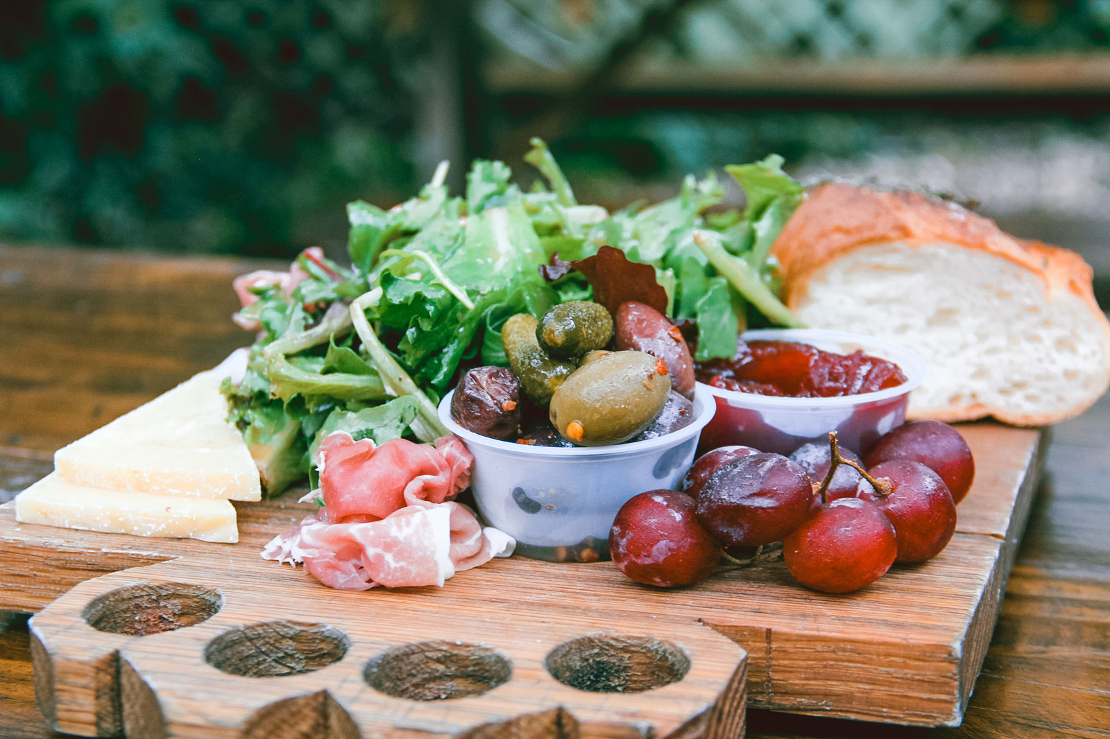 Meat and cheese board with bread, lettuce and grapes.