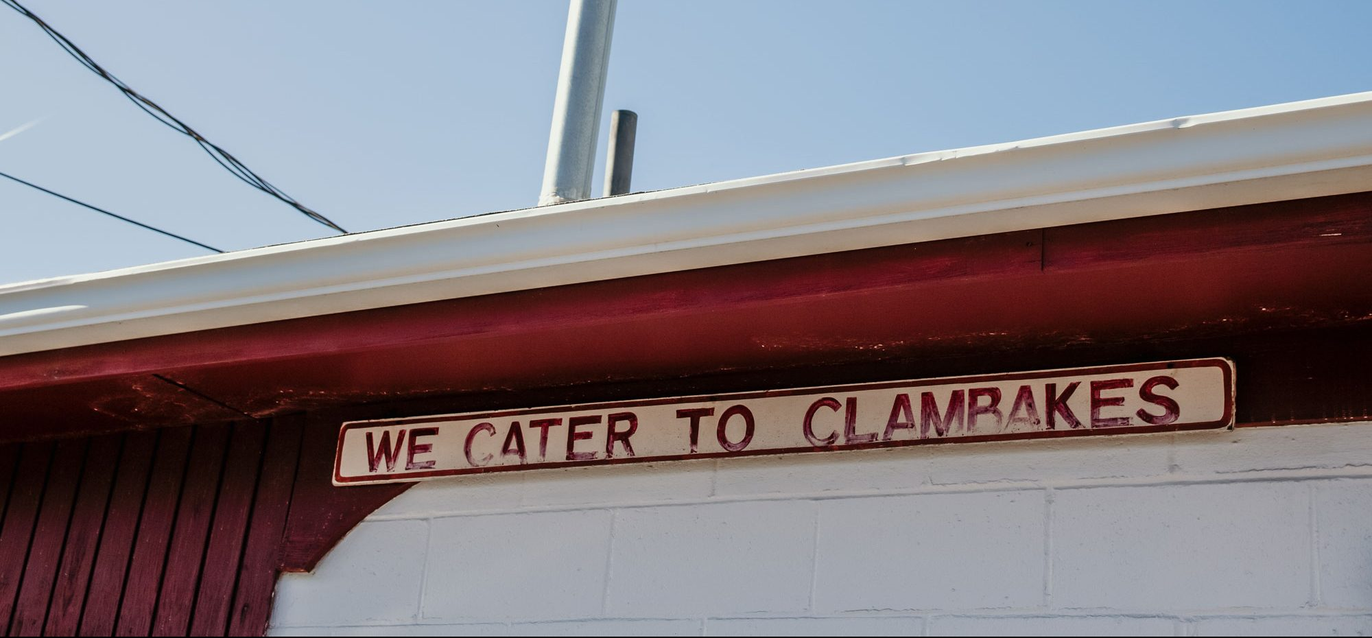 An old, faded sign of Woodman's Clam Strip.