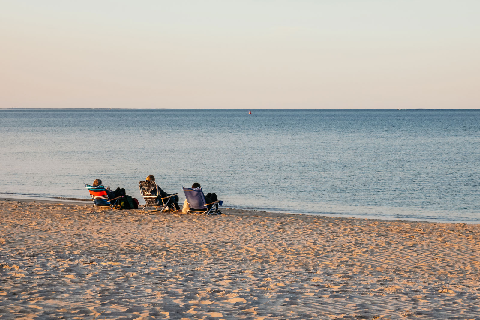 Three people relaxing in folding chairs on Crain's Beach.