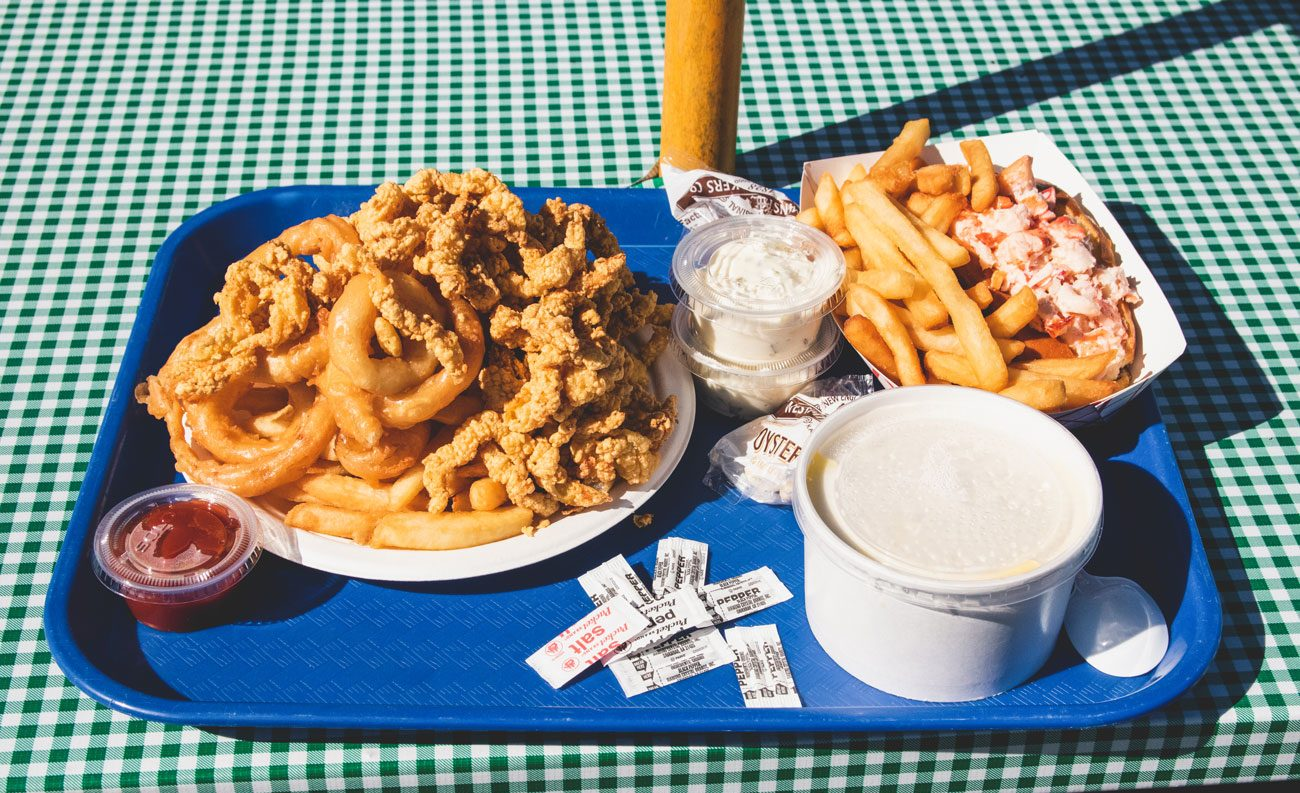 A tray filled with fried clams, french fries and other fried eats of Woodman's.