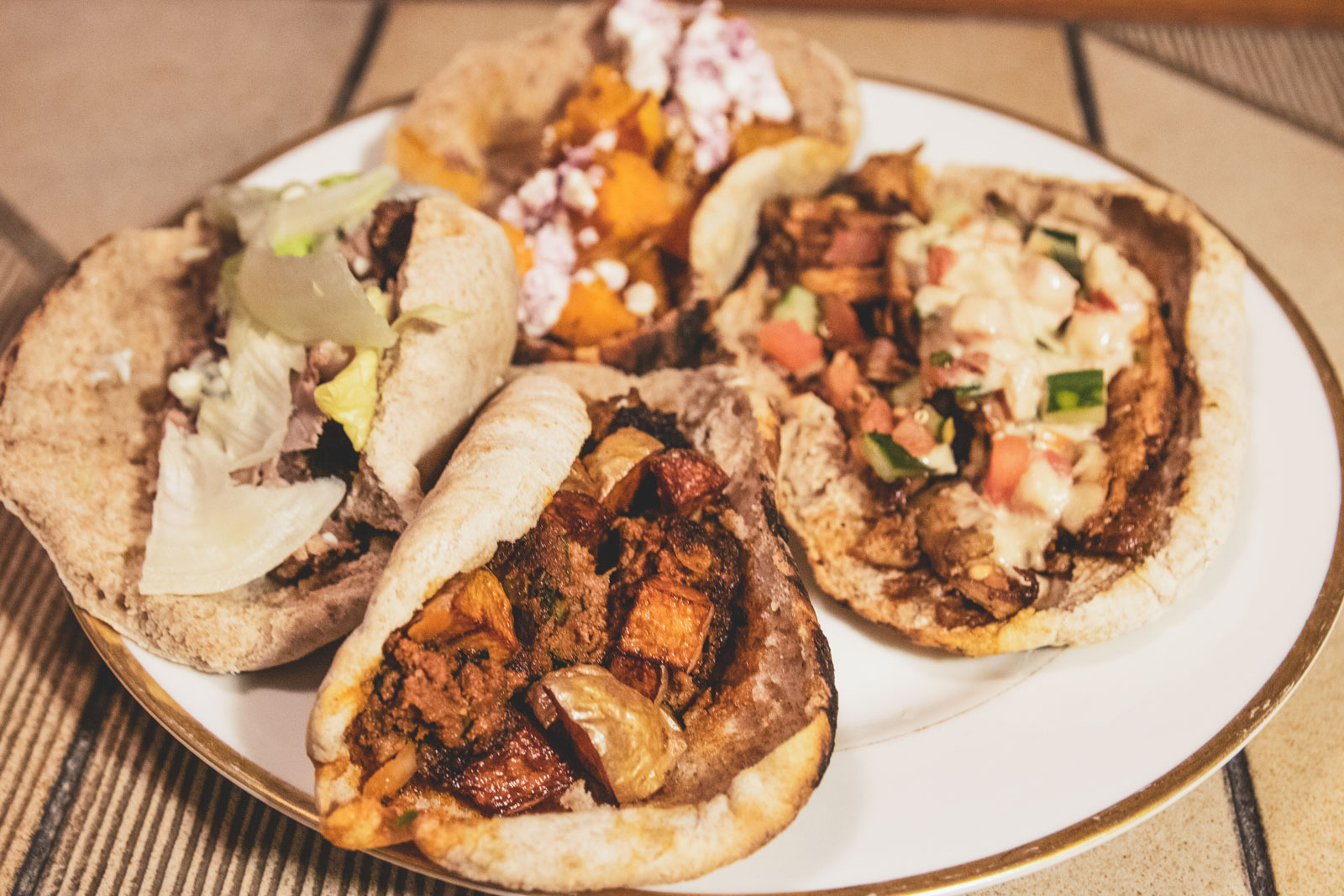 A plate filled up with a variety of different shwarma wraps.
