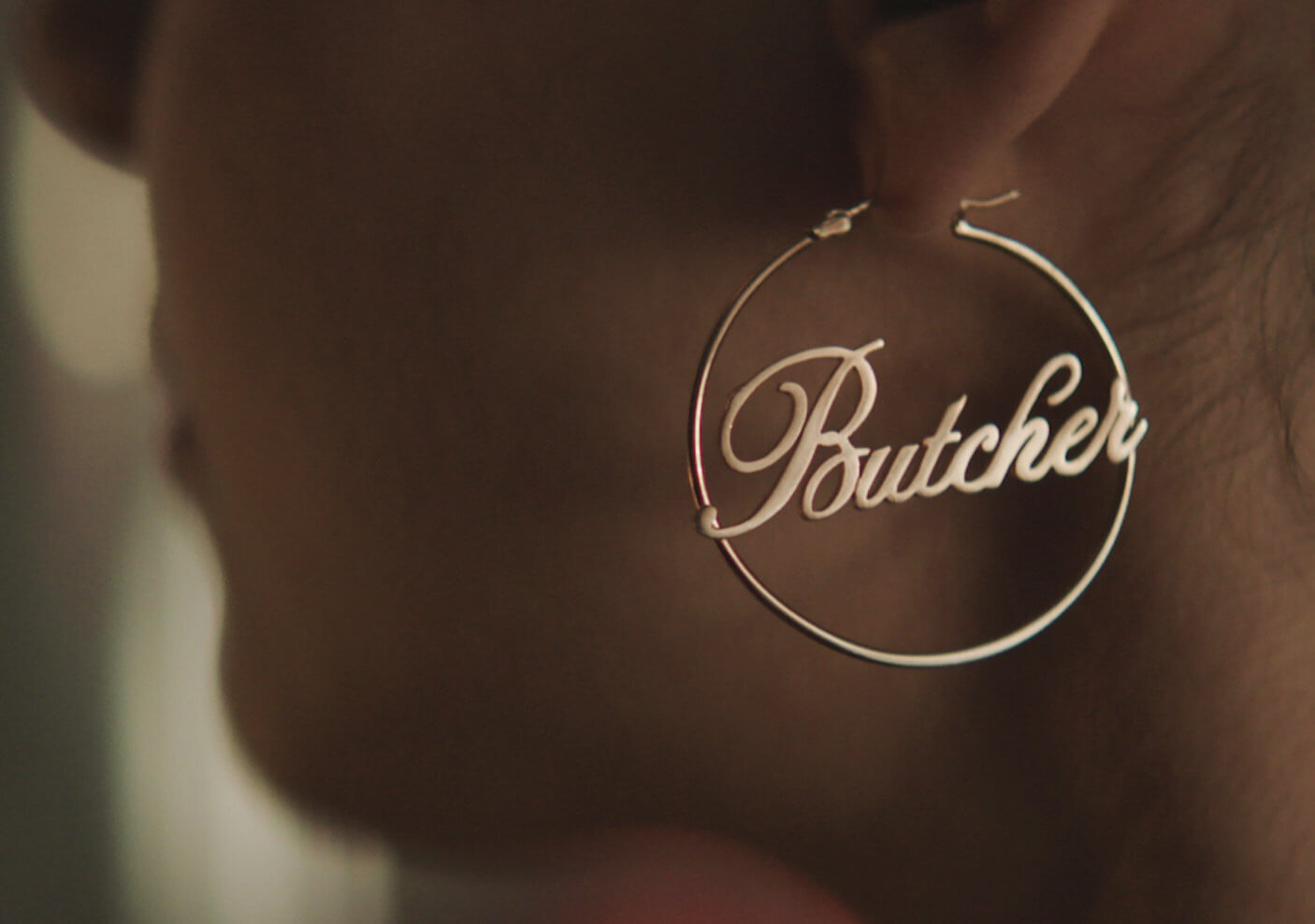 A golden hoop earring with a cursive Butcher in center.