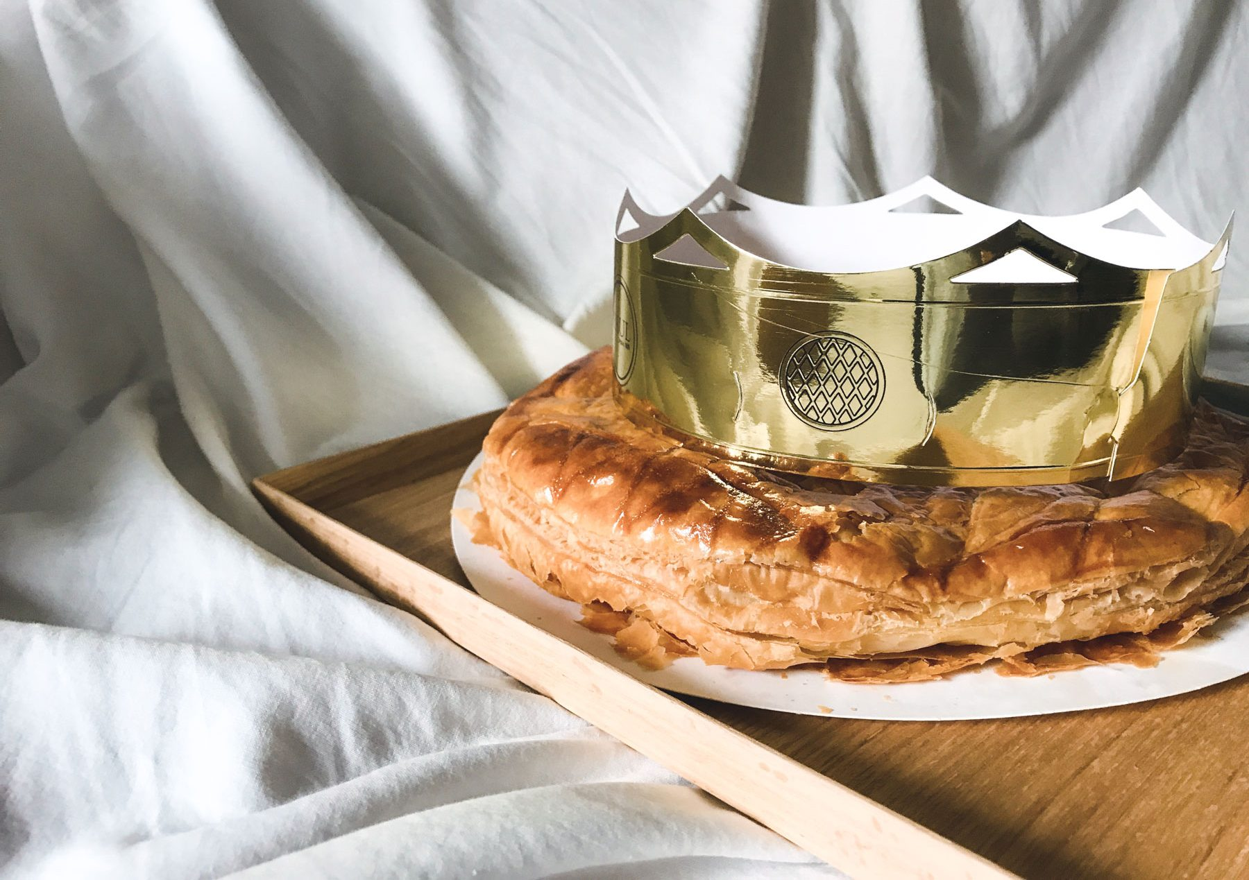 A buttery galette des rois adorned with a shiny paper crown.