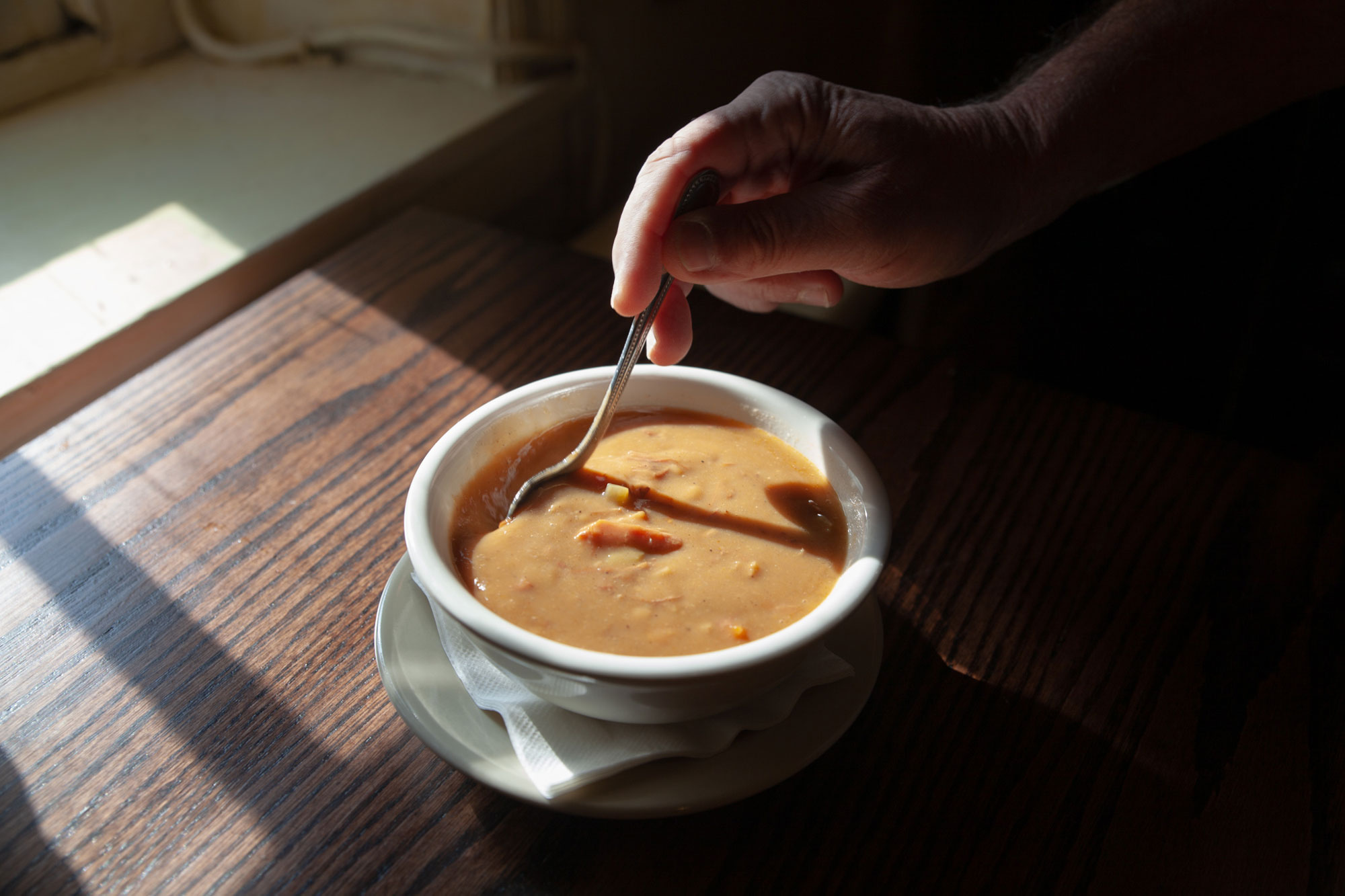 A person stirring a spoon in a small bowl of snapper soup.
