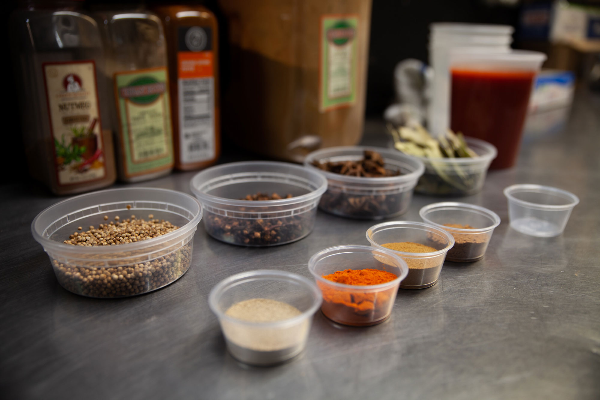 Small containers filled with a variety of spices and seasonings for snapper soup.
