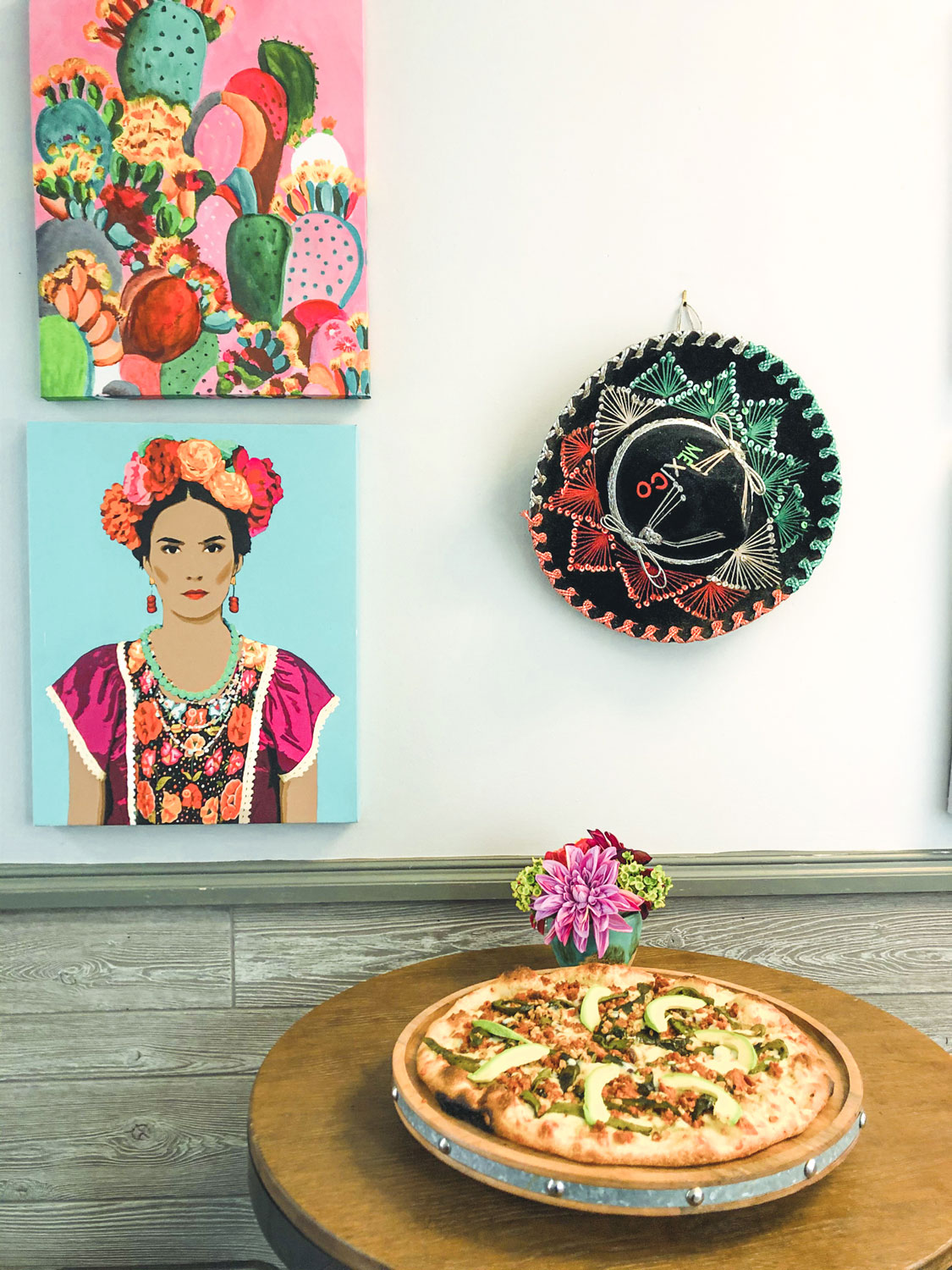 Mexican pizza accompanied by vibrant, colorful Mexican art.